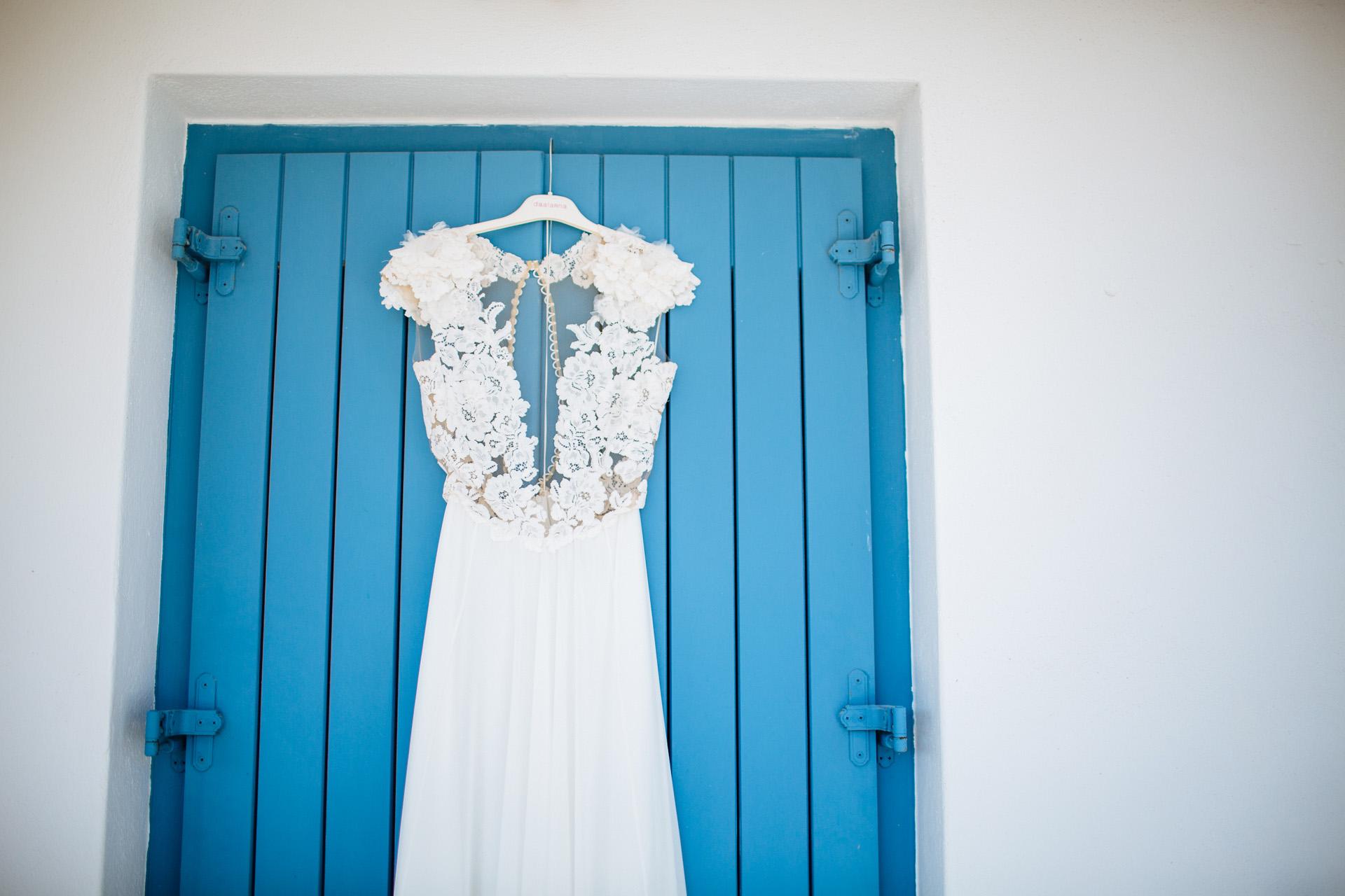 wedding dress hanging up against blue door
