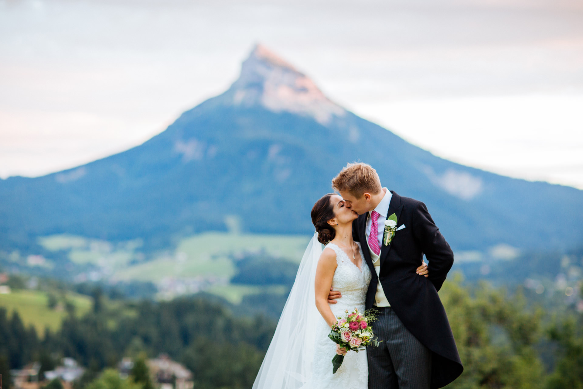 bride and groom kiss in front of mountain backdrop