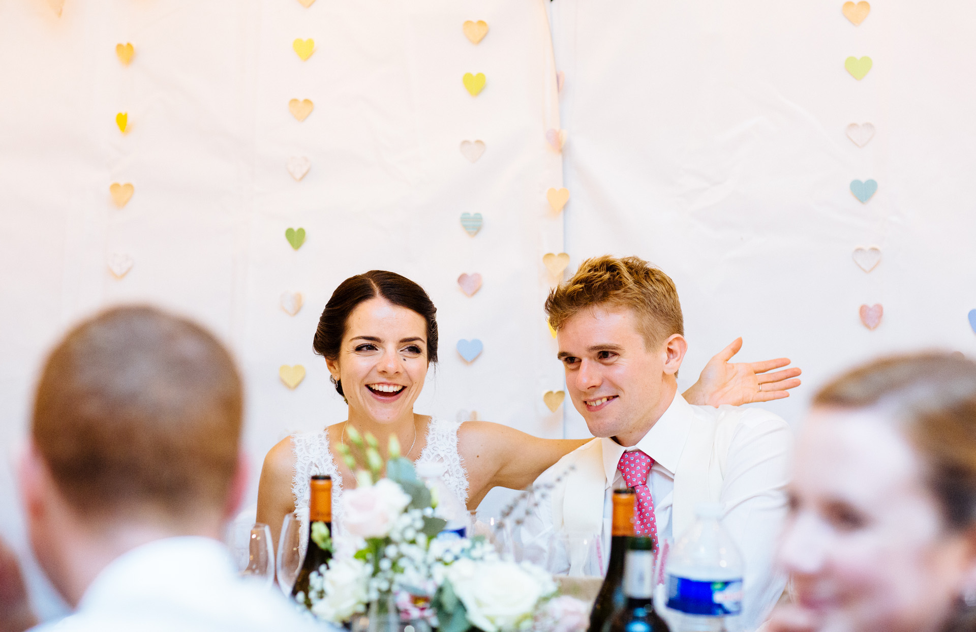 bride and groom reacting to speech in wedding marquee