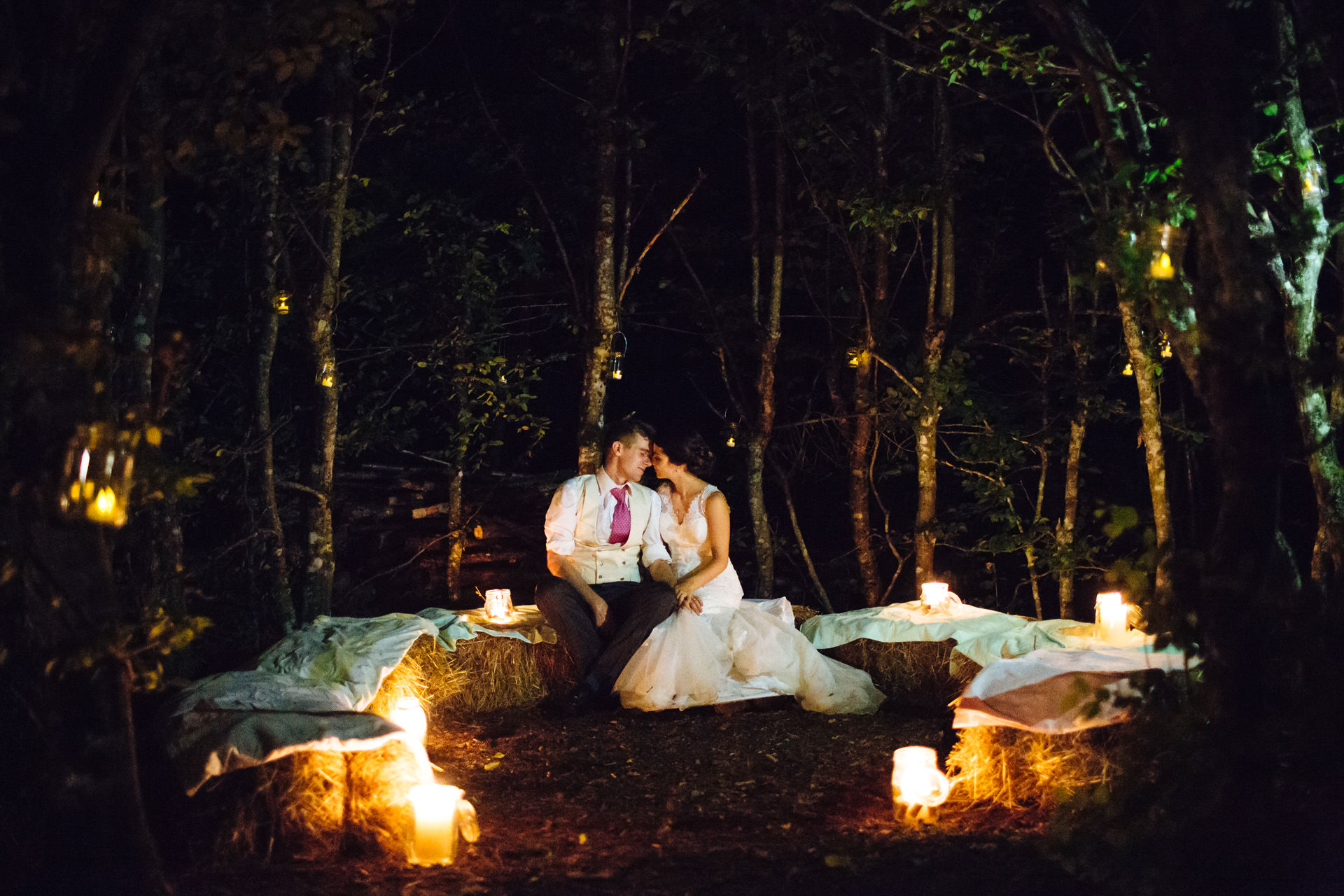 bride and groom candle lit wood at night