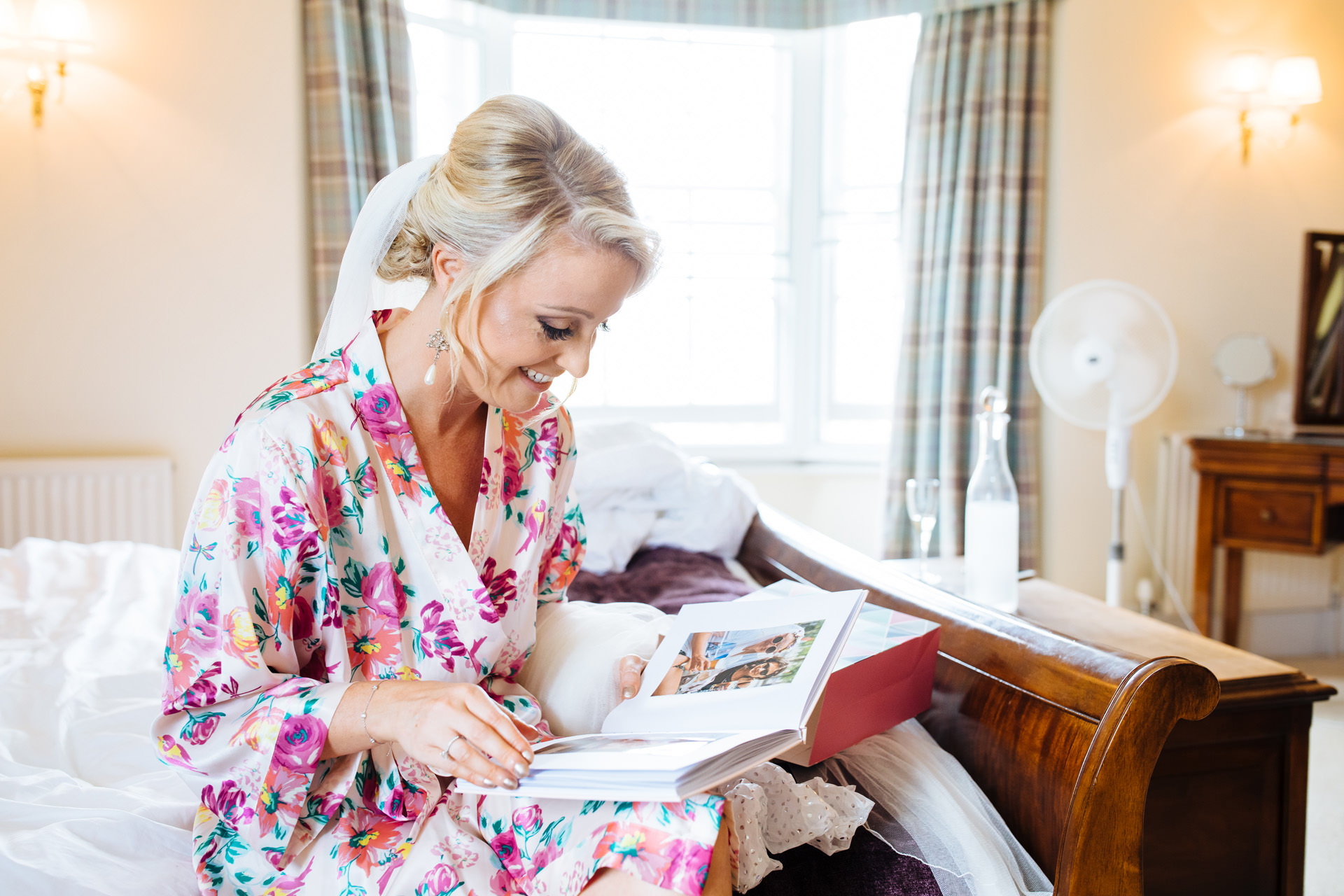 bride in floral dressing gown and veil reads surprise photo album