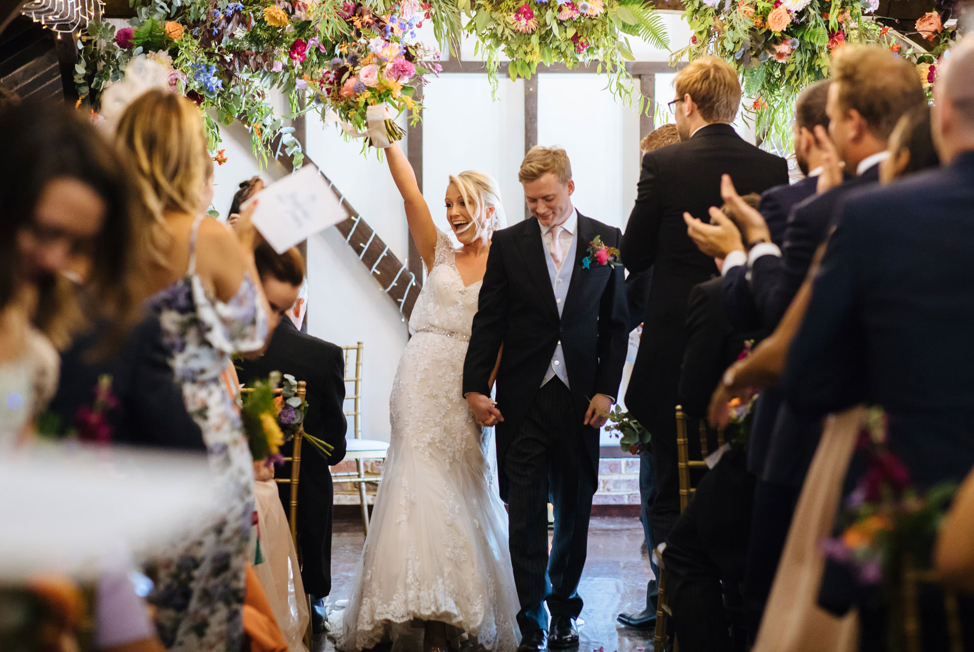 bride throwing bouquet up in the air in joy as they walk back down the aisle
