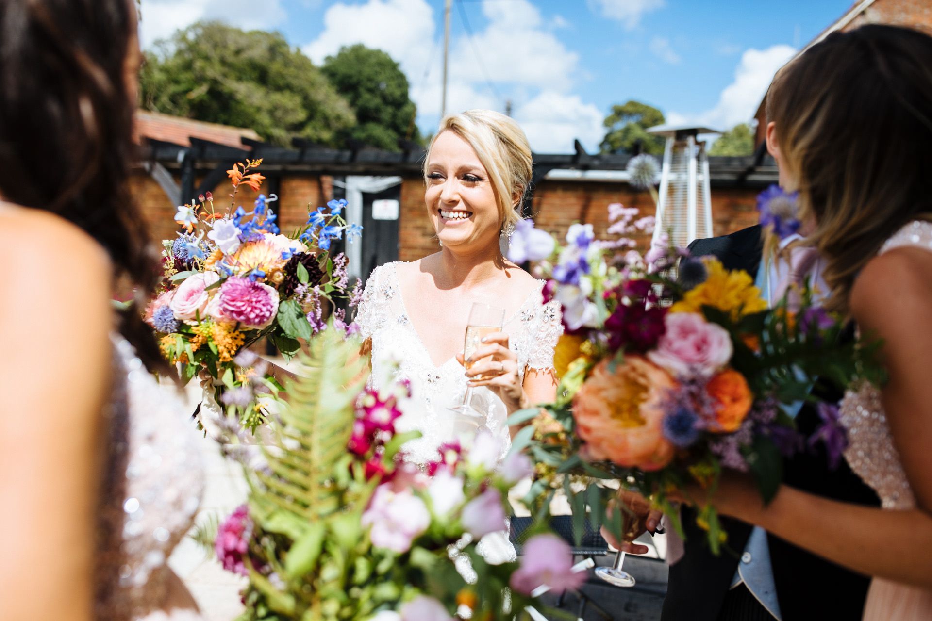 bride smiling with bright flowers and champagne at black stockcountry estate