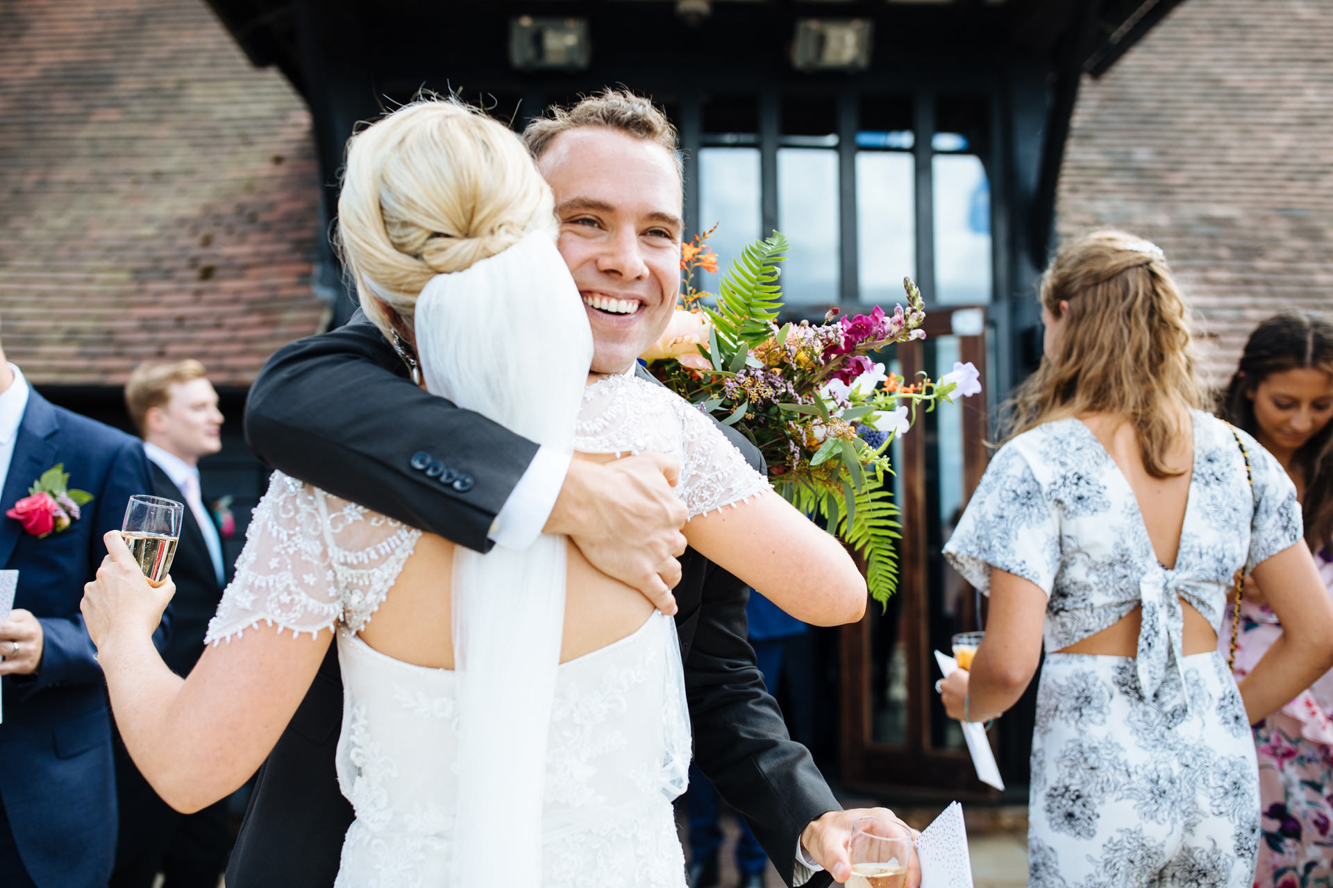 man with brown hair hugging bride smiling