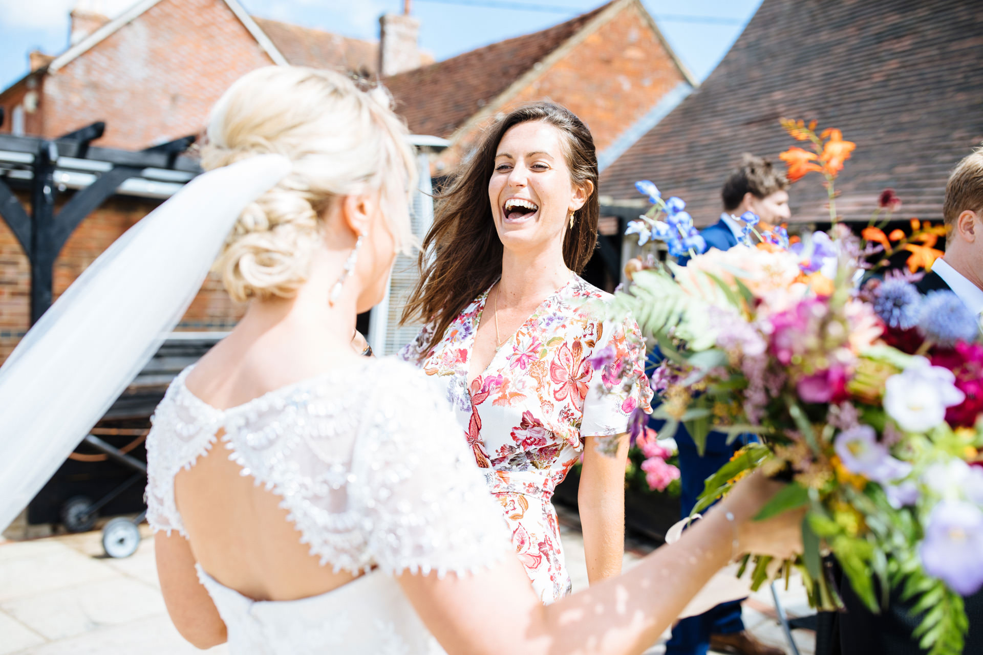 wedding guest in floral dress laughing at the bride