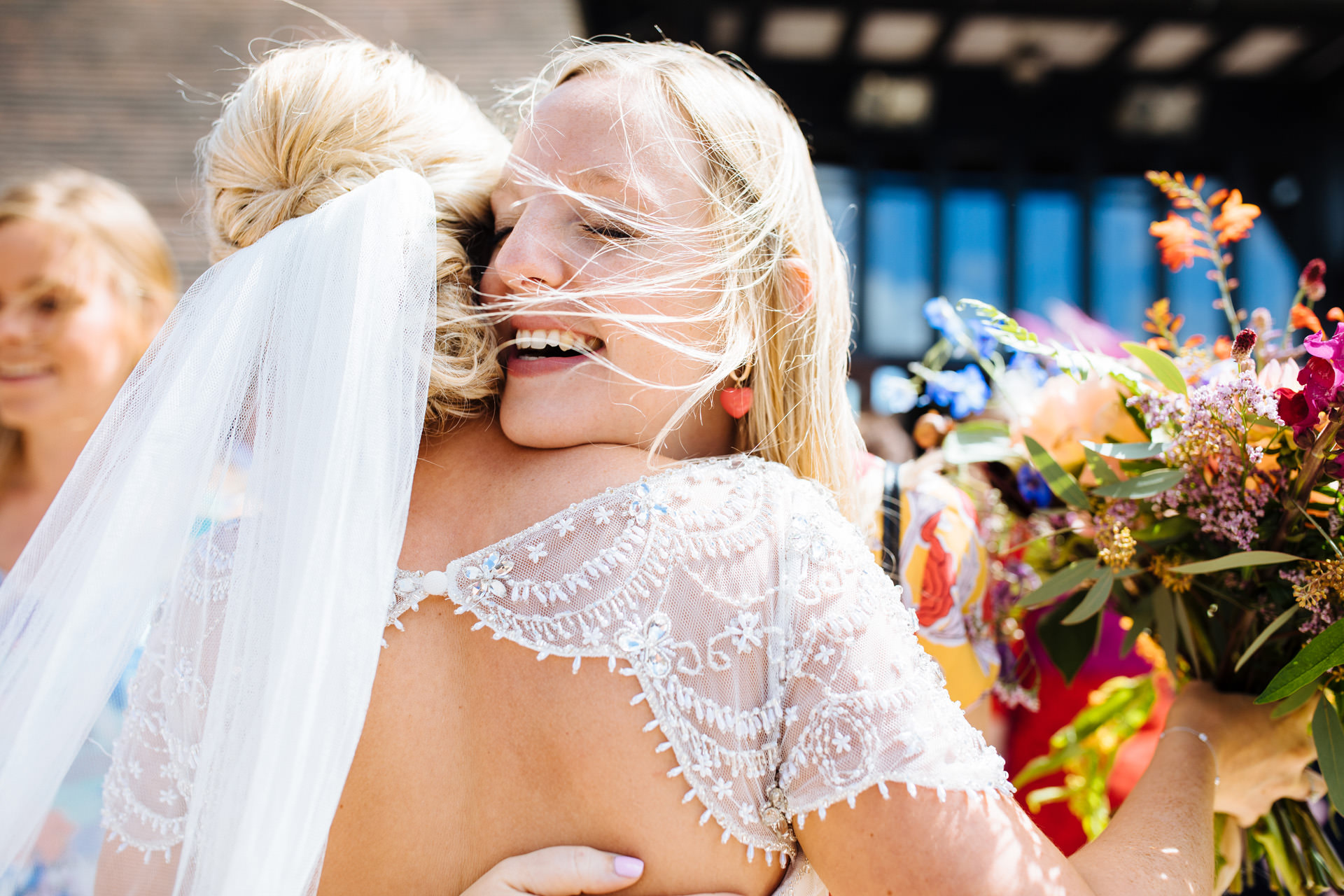 wedding guest with blonde hair and red earrings hugging bride smiling