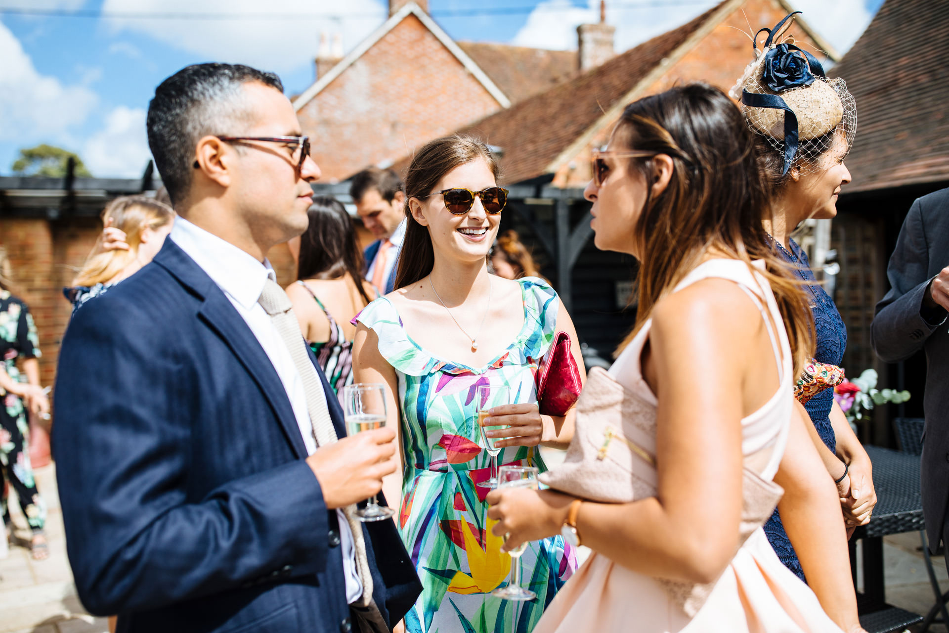 wedding guest with brown hair and sunglasses smiling