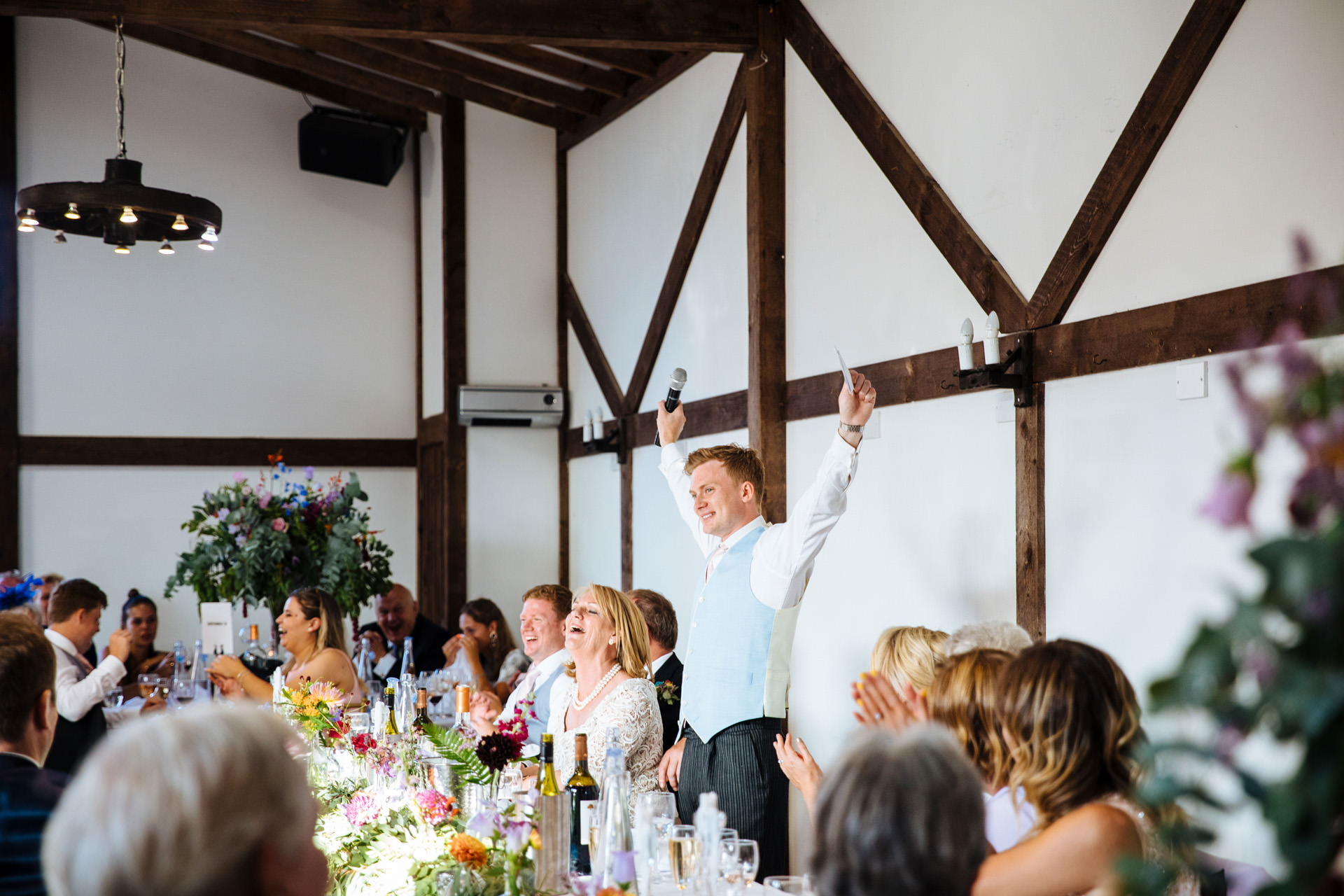 groom putting his hands up in the air cheering during wedding speech