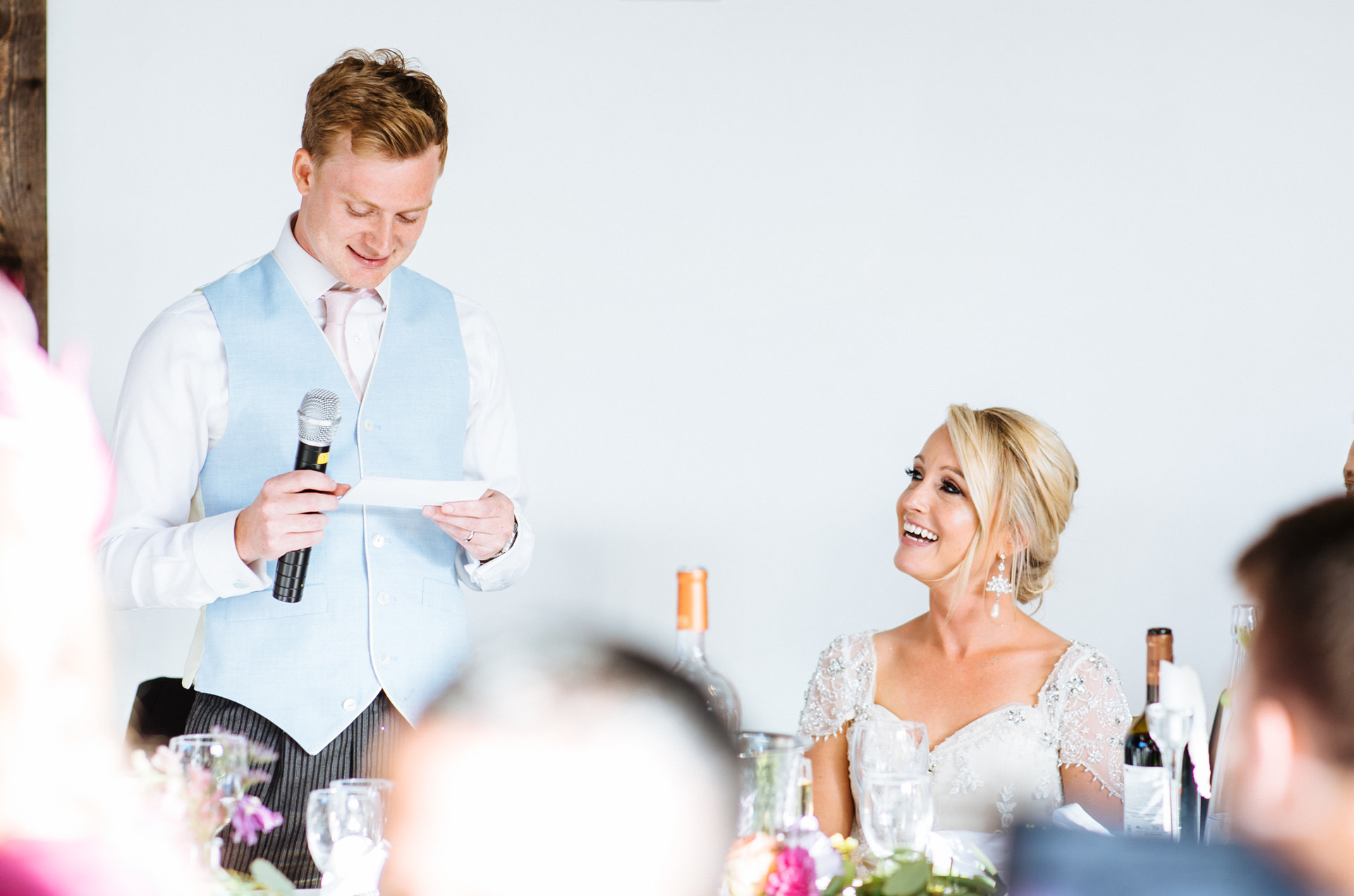 bride smiling and looking up at groom during his speech at Blackstock country estate