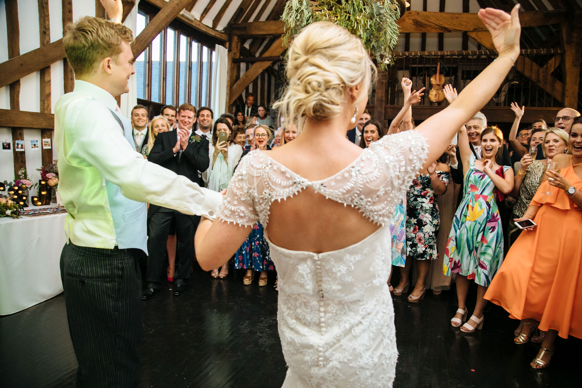 bride and groom signal for their guests to join them on the dance floor