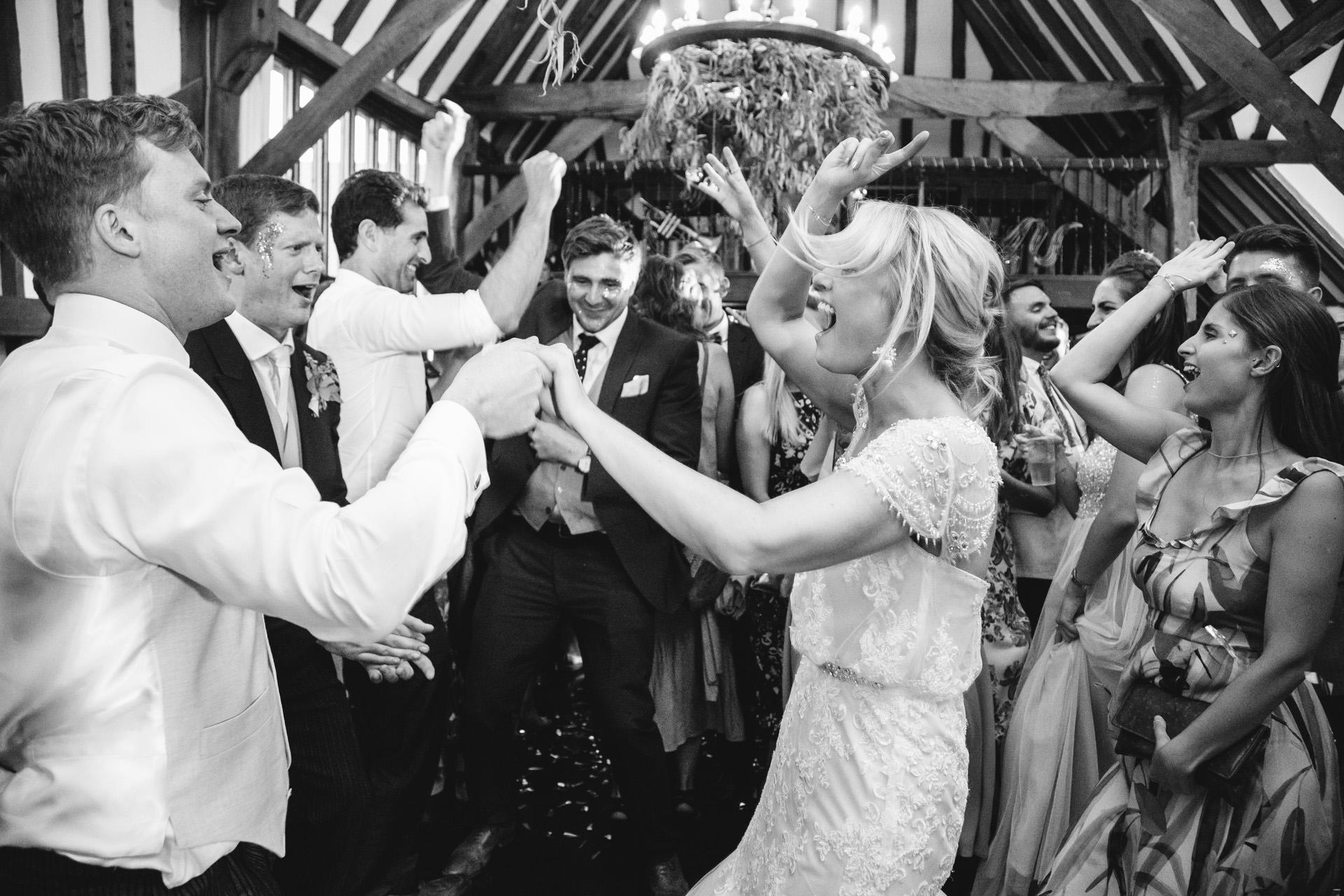 bride and groom jumping and partying with their friends in barn