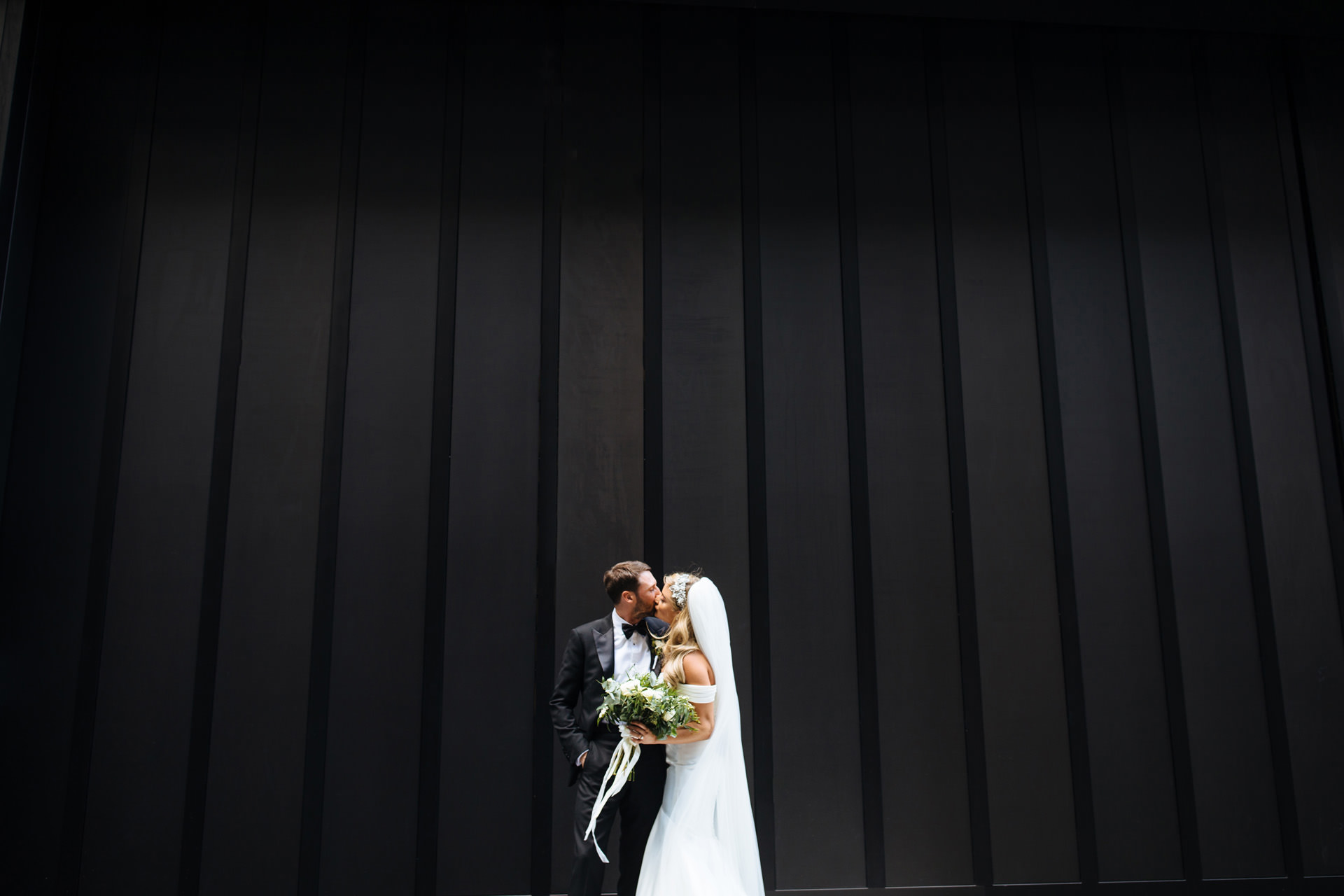 bride with blonde hair and long veil and groom in a tux having a kiss in front of huge urban black doors