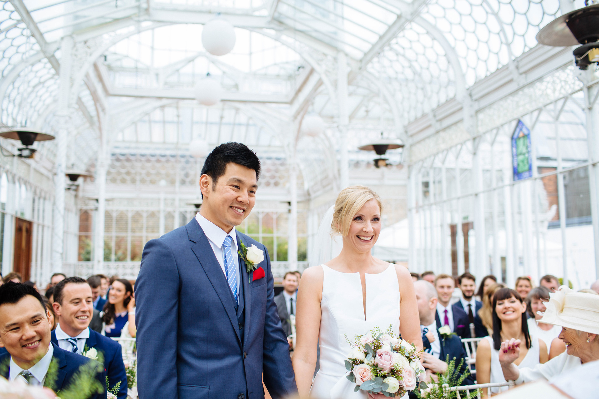 bride and groom smiling in wedding ceremony in a big glass greenhouse