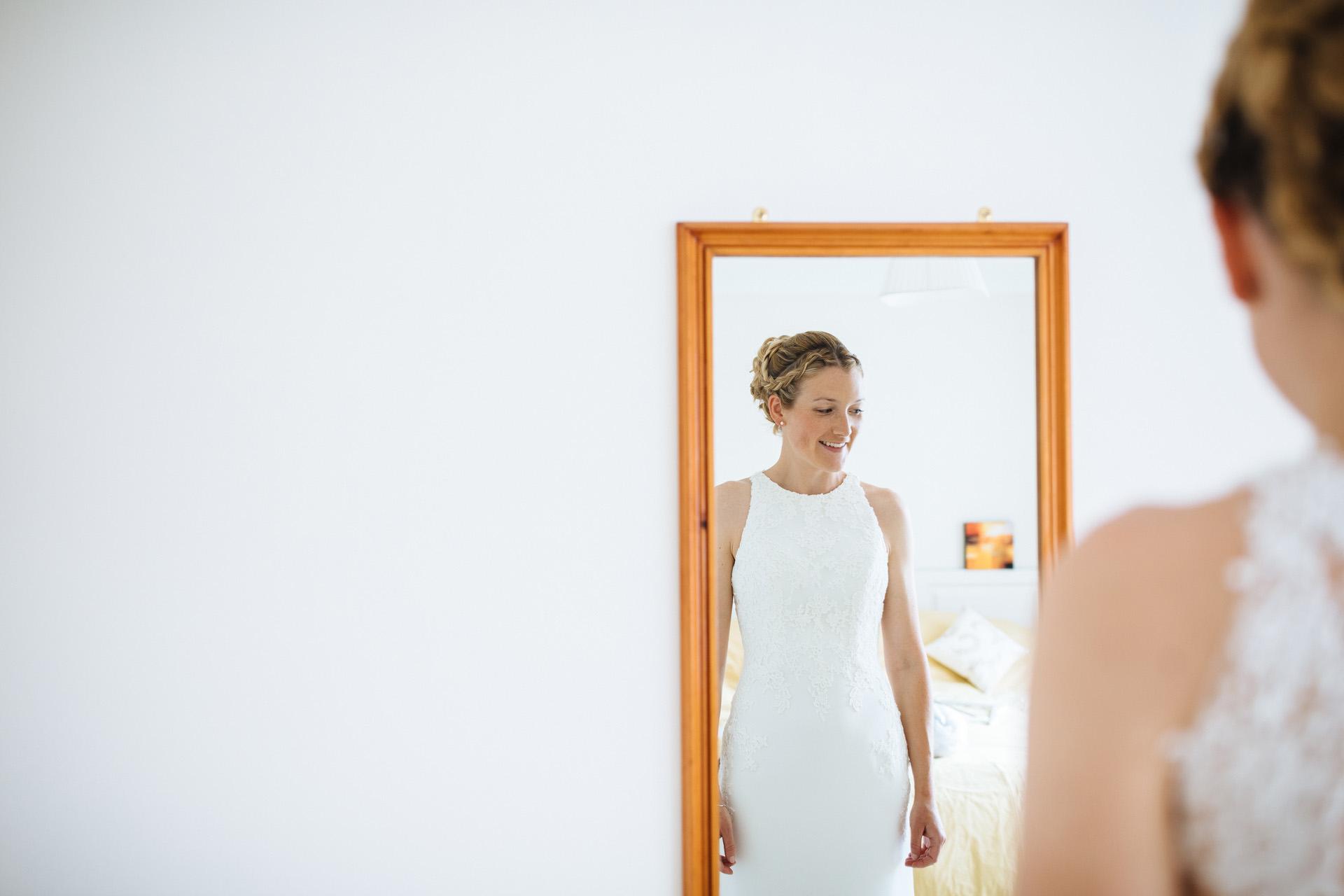 bride watching wedding dress go on in mirror