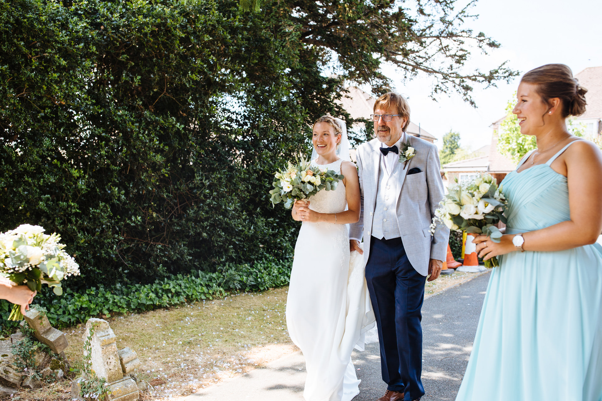 bride in elegant dress arriving with her dad in suit and bow tie