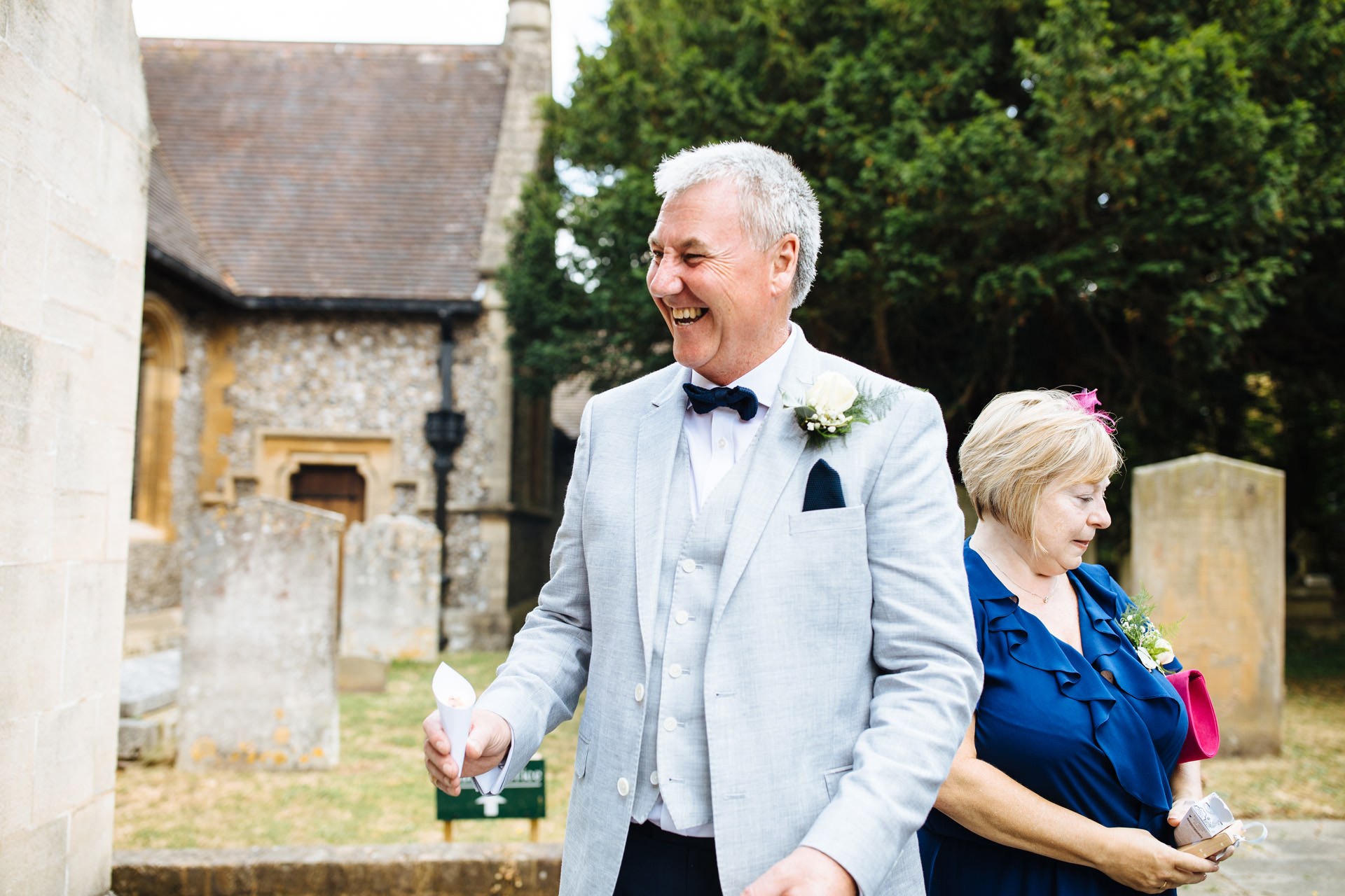 father of the bride outside the church holding confetti cone while laughing