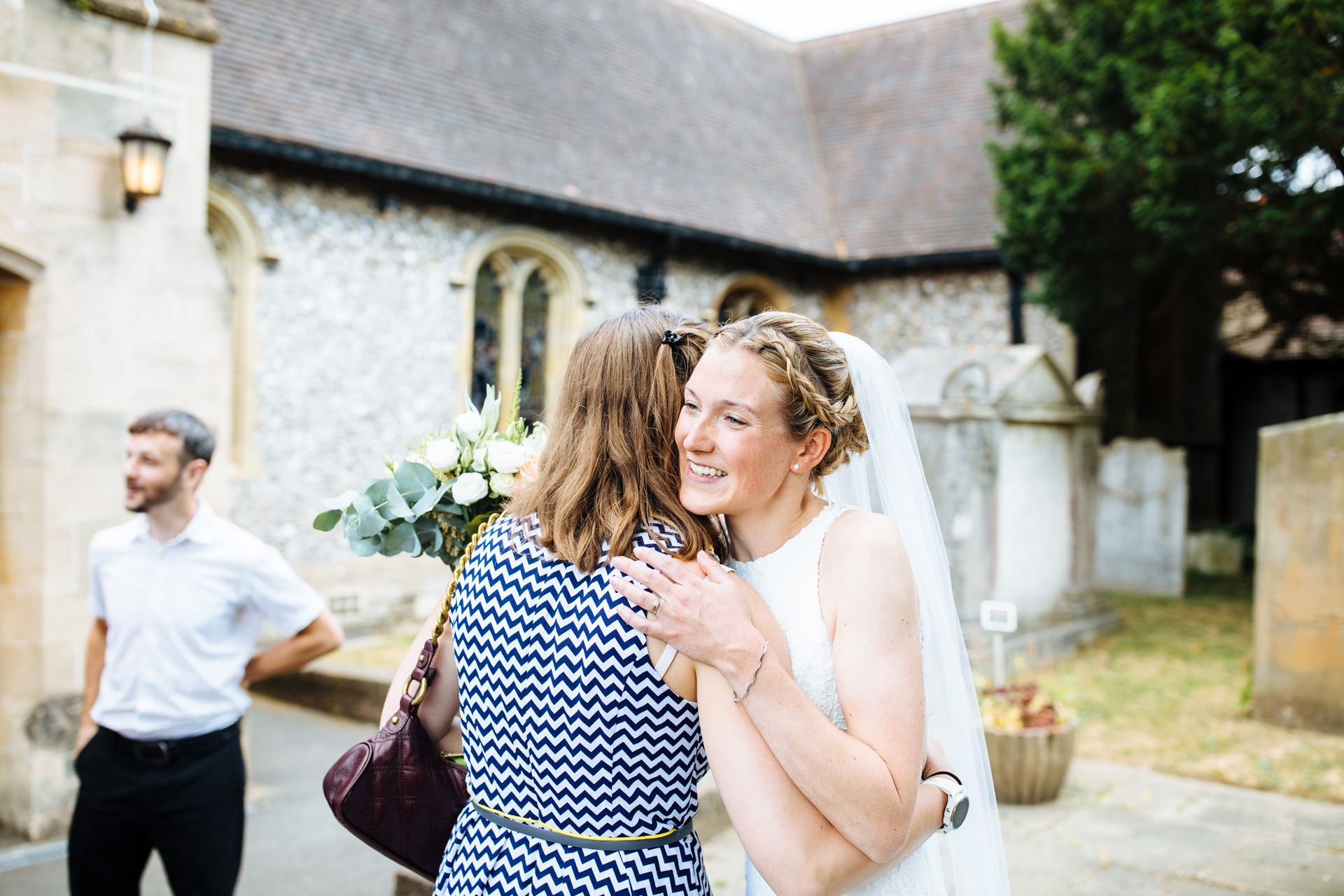 bride smiling and hugging lady in striped dress outside church