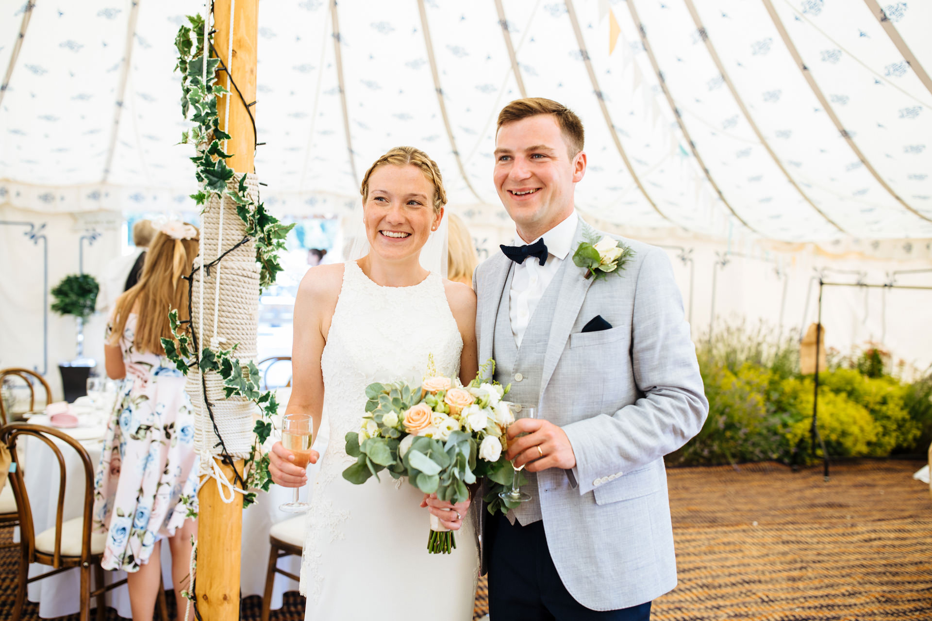 bride and groom posing for picture in the marquee and smiling at kentfield farm wedding