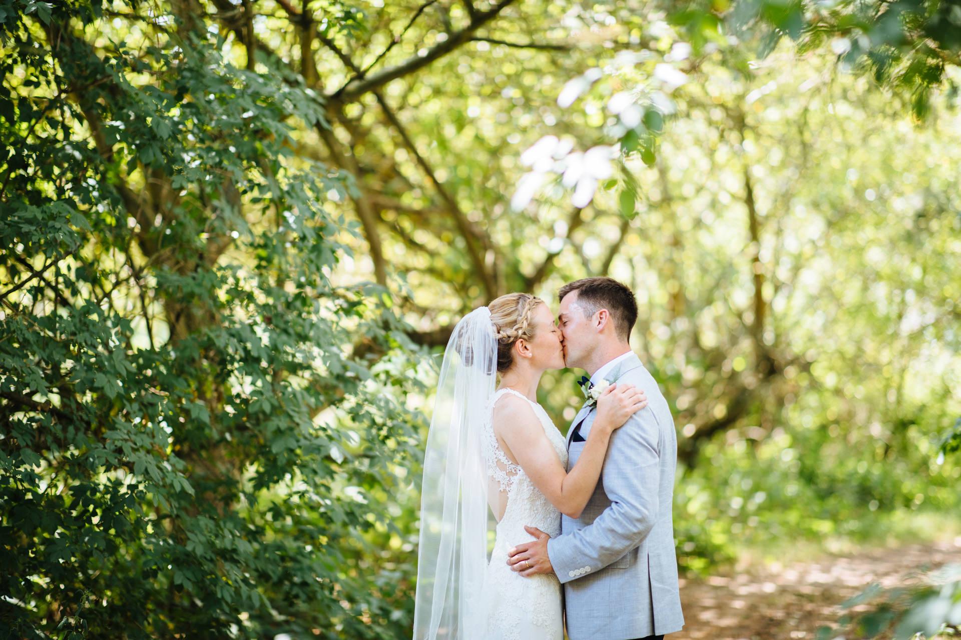 bride and groom kissing in sun lit woodland at kentfield farm wedding
