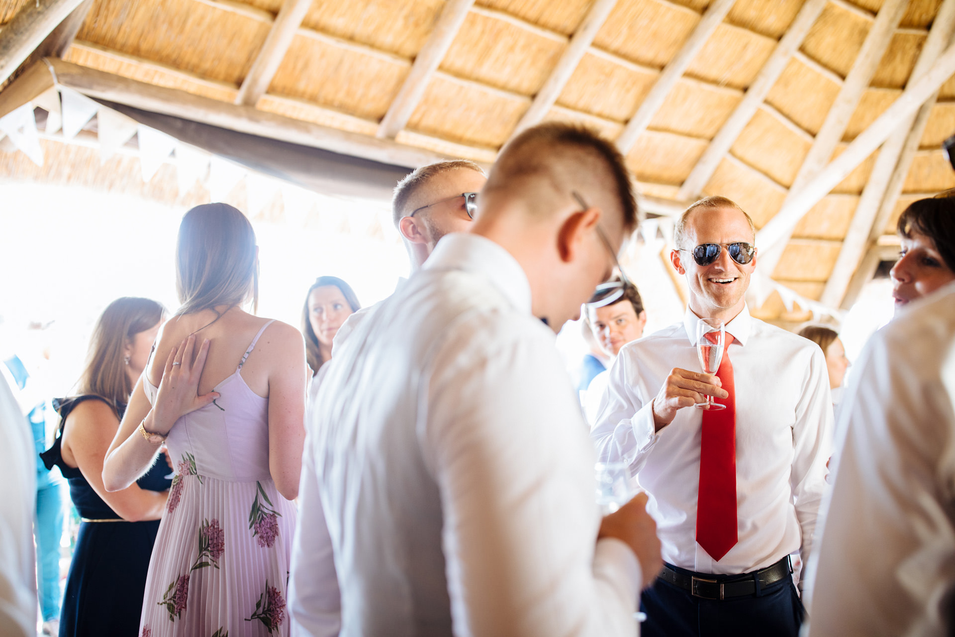 man in red tie and sunglasses smiling with champagne in the barn
