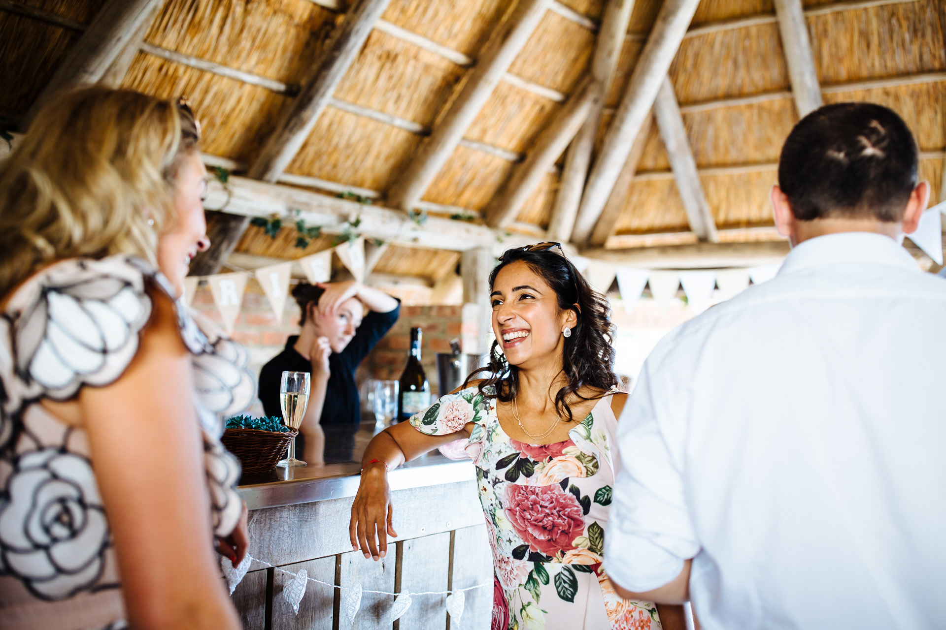 lady in floral dress leaning against the bar in the barn smiling