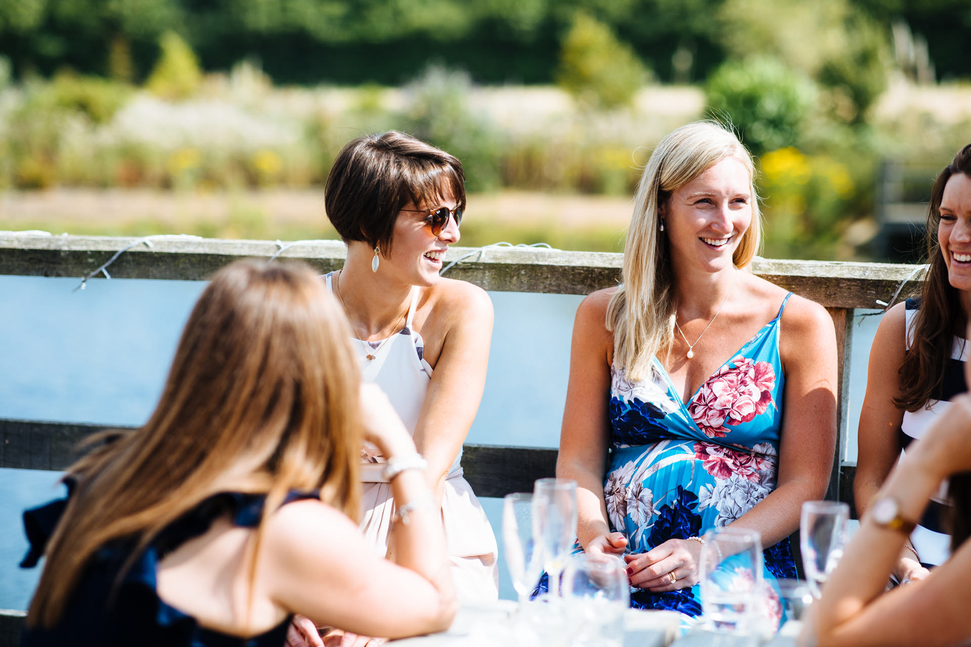 female wedding guests sitting down laughing with lake in background