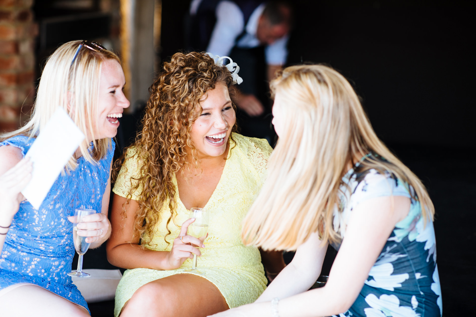 three female wedding guests dressed in blue and yellow laughing with each other