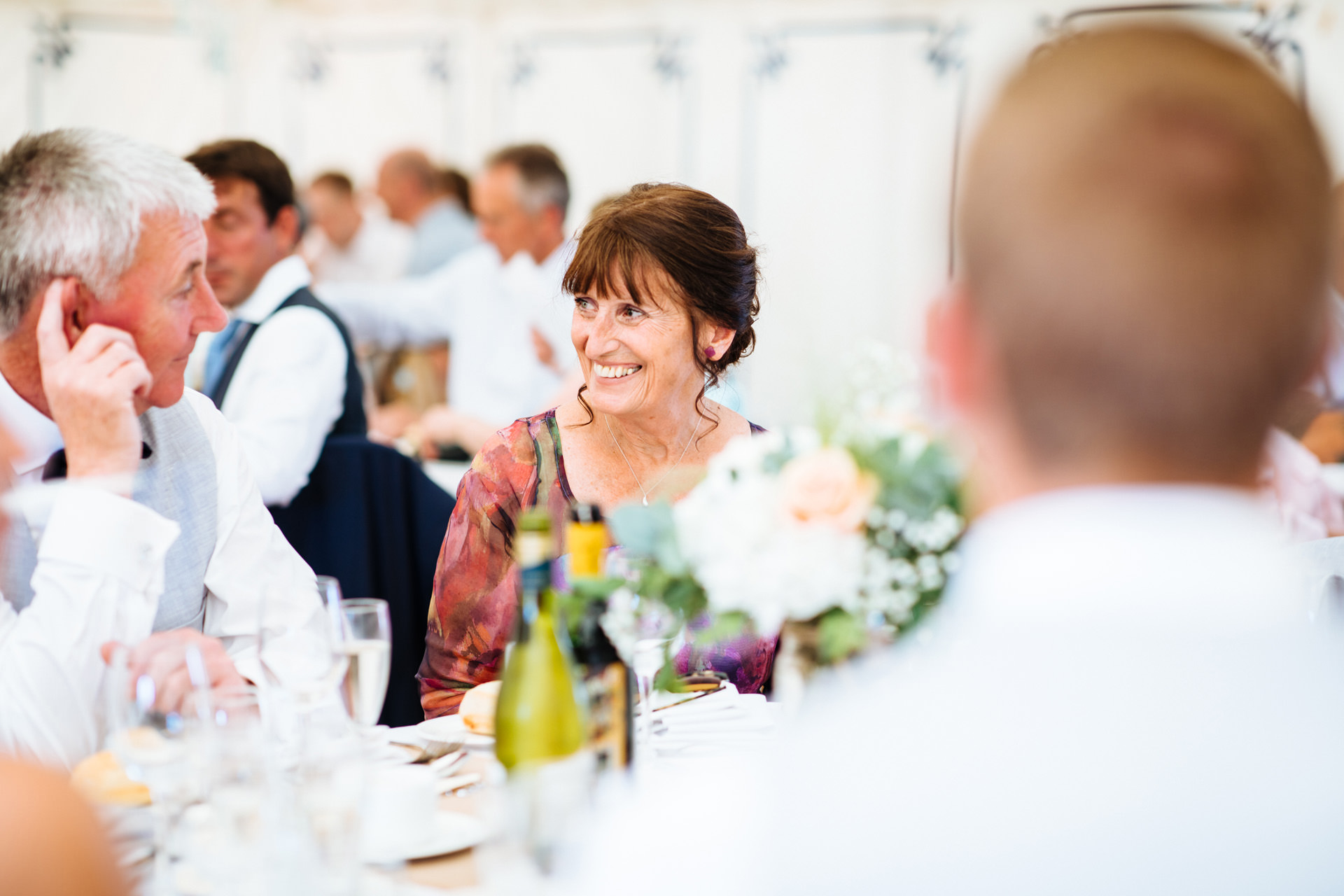 brides mum with brown hair and purple dress smiling at dinner table
