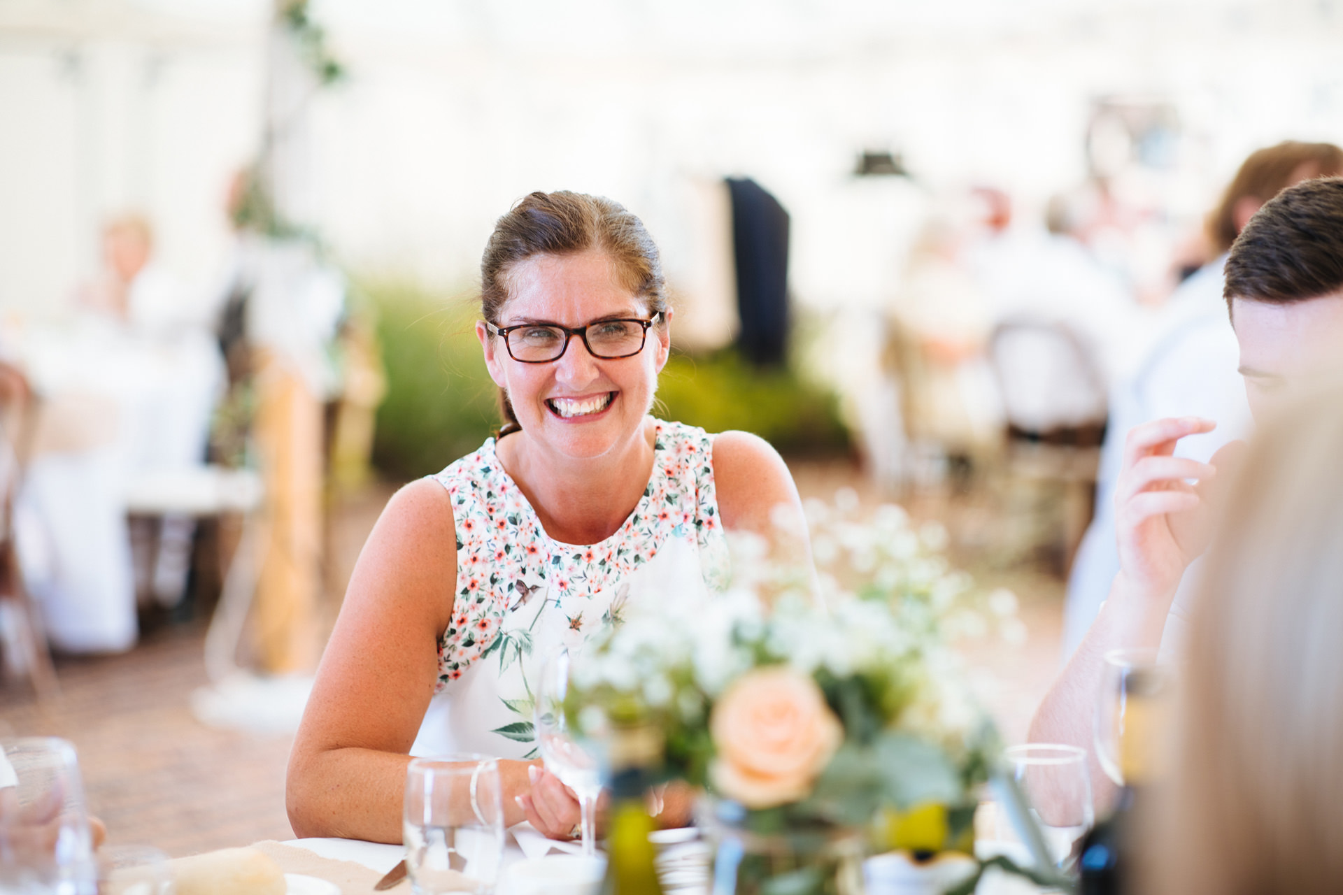 lady in glasses and floral dress beaming across dinner table