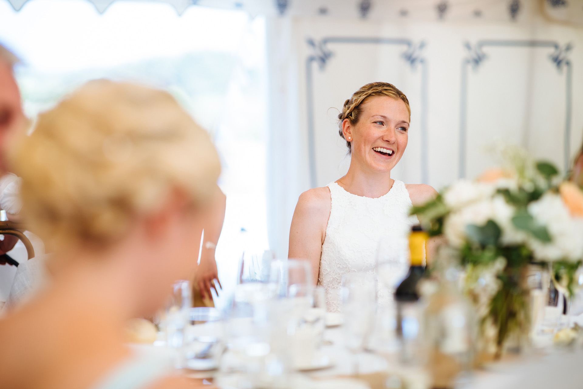 bride with blonde hair tied up in plait laughing at her dads speech at kentfield farm wedding