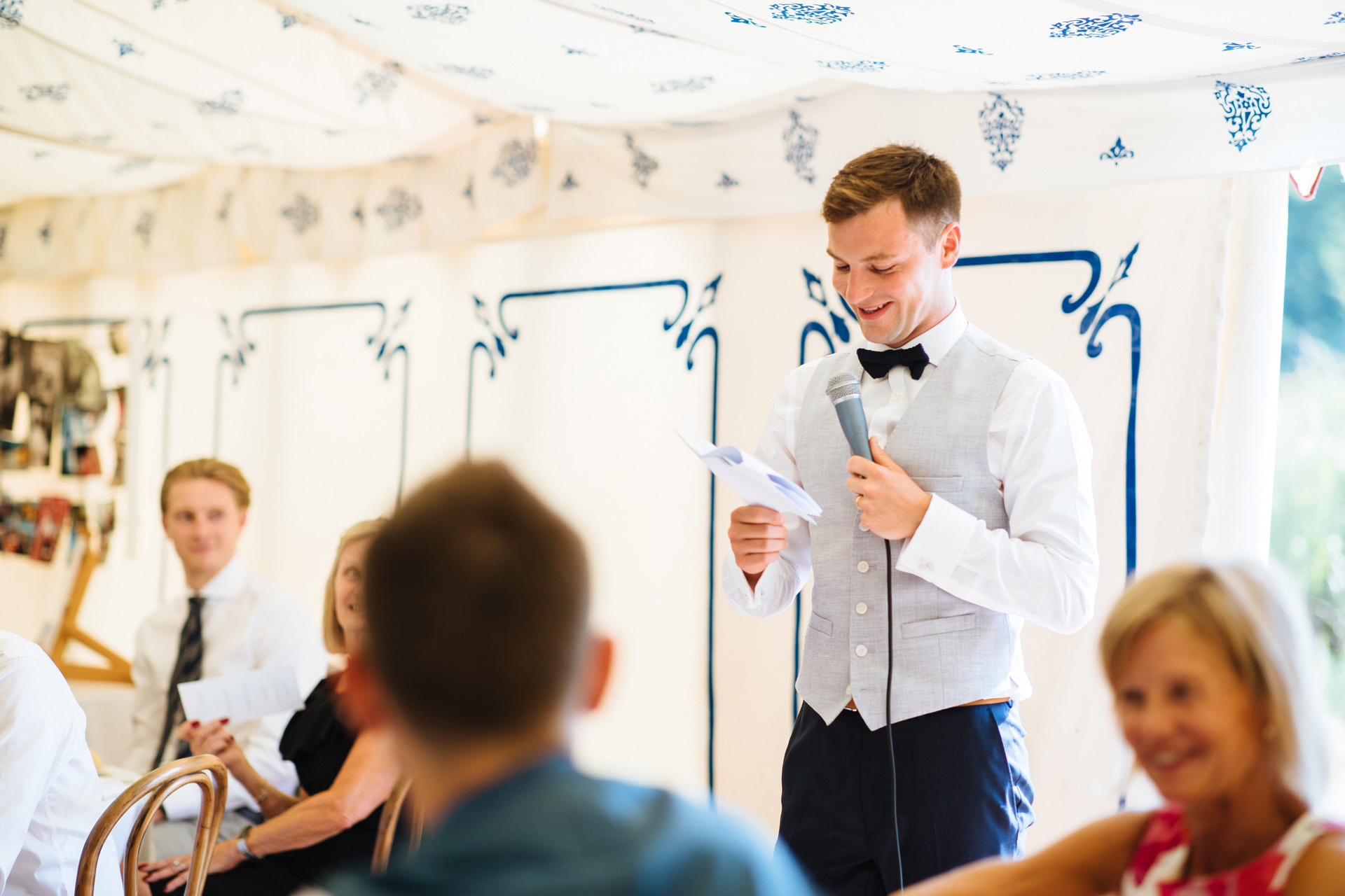 groom in navy bow tie giving speech in sailcloth tent at kentfield farm wedding