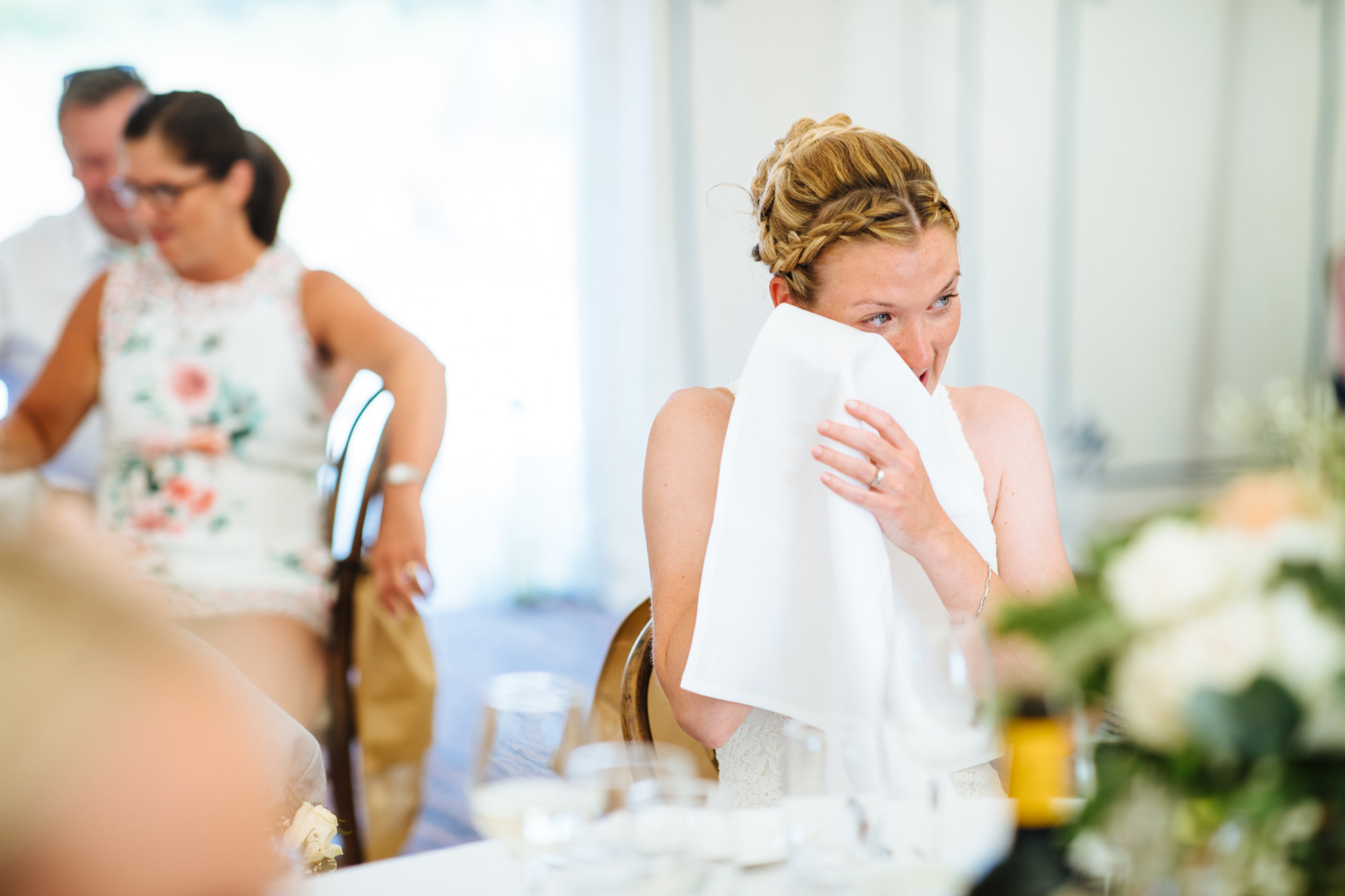 bride wiping away a tear with napkin at wedding speech