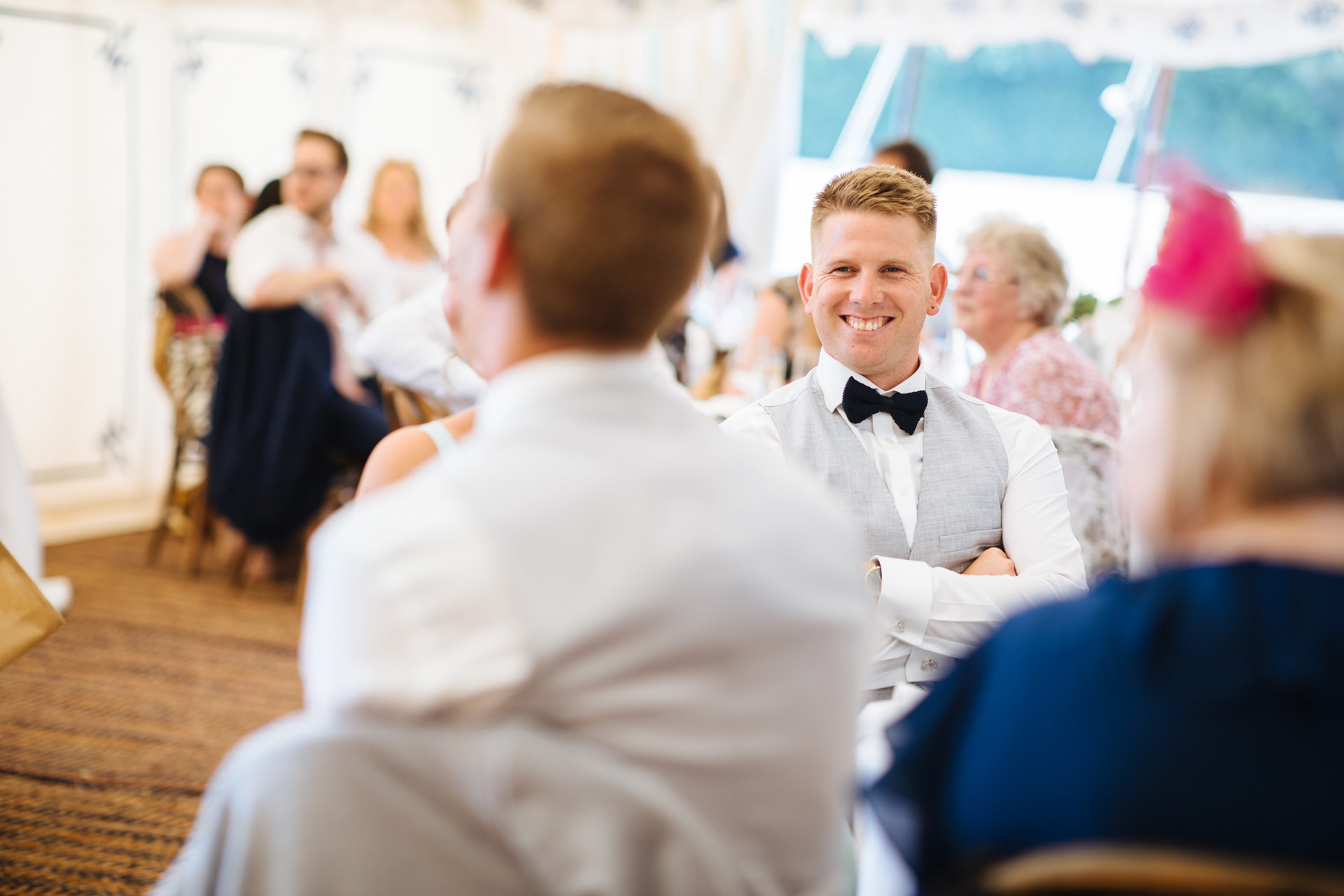groomsman in a bow tie smiling at speech
