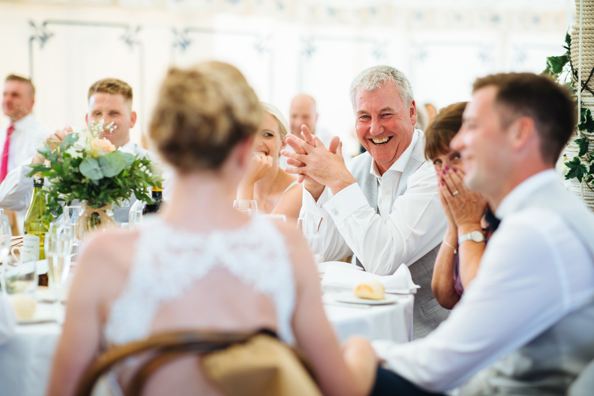 grooms dad laughing at the bride during the speeches