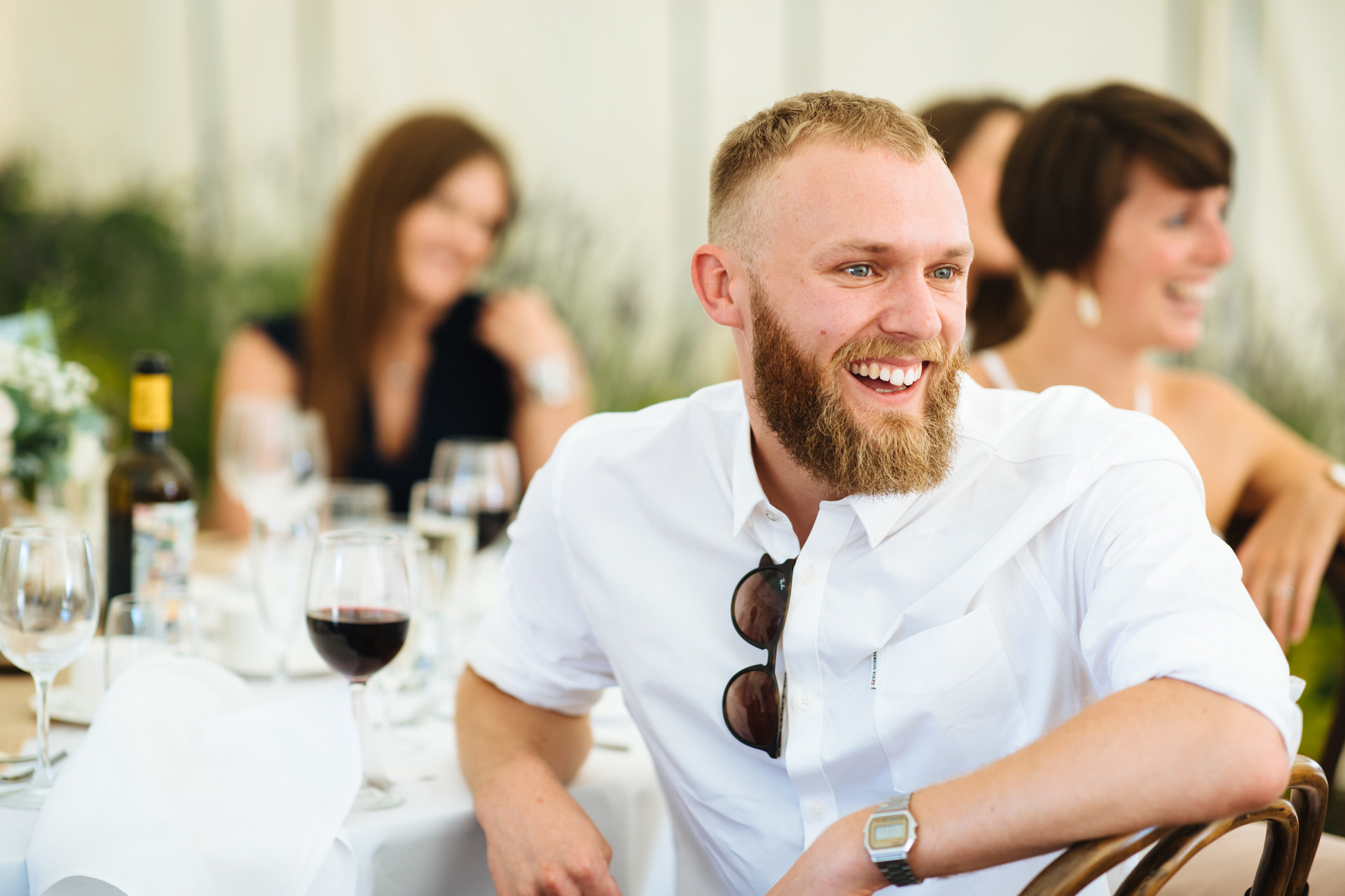 wedding guest with beard and sunglasses laughing at speeches