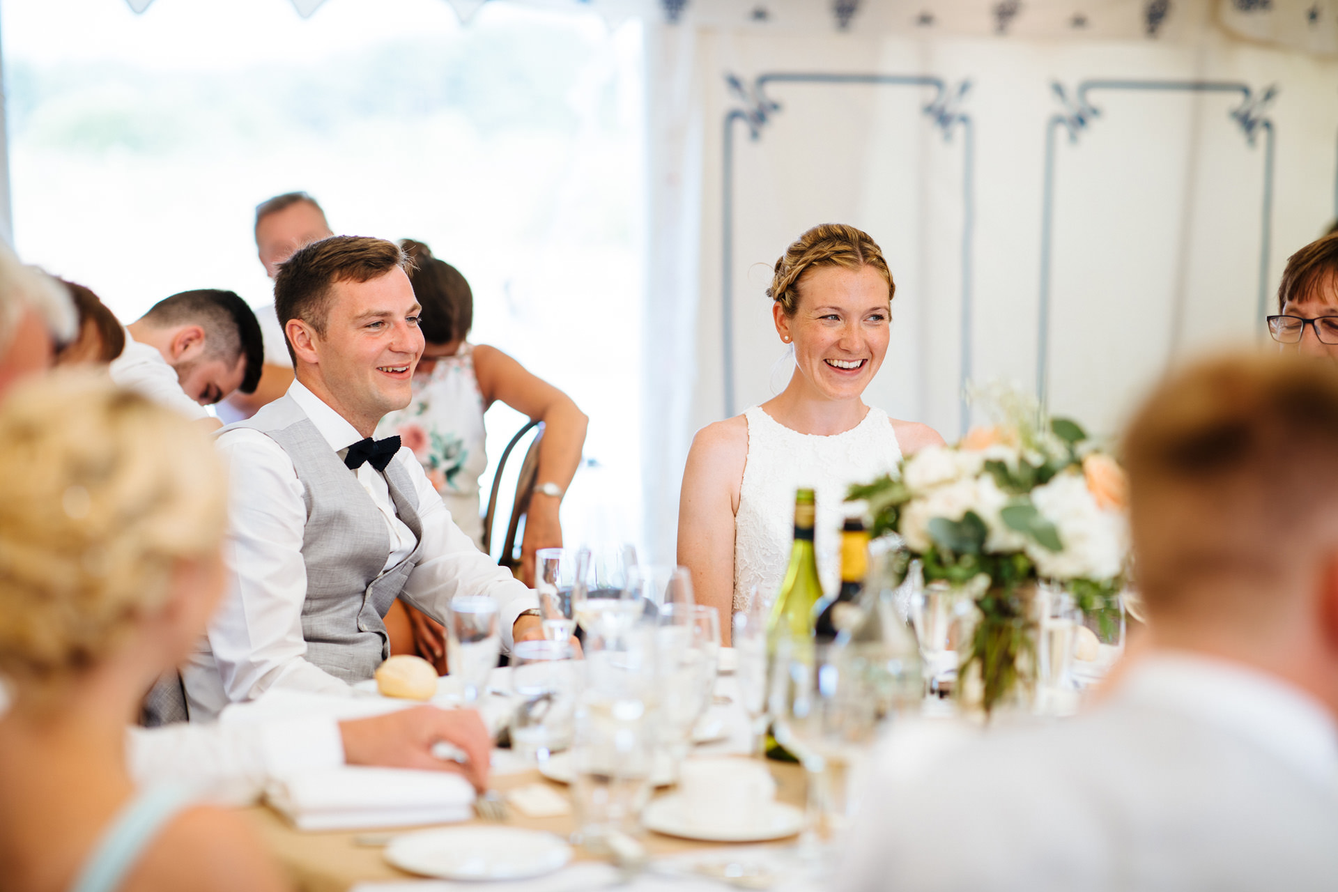 bride and groom sitting down in marquee smiling and listening to speech at kentfield farm wedding