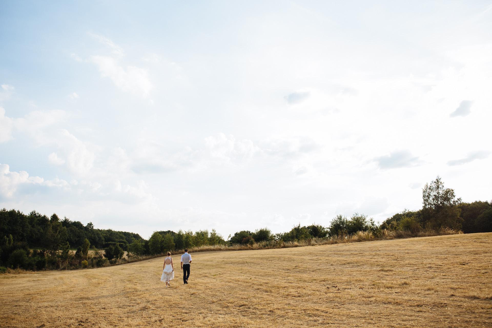 bride and groom walking in corn field at sunset at kentfield farm wedding