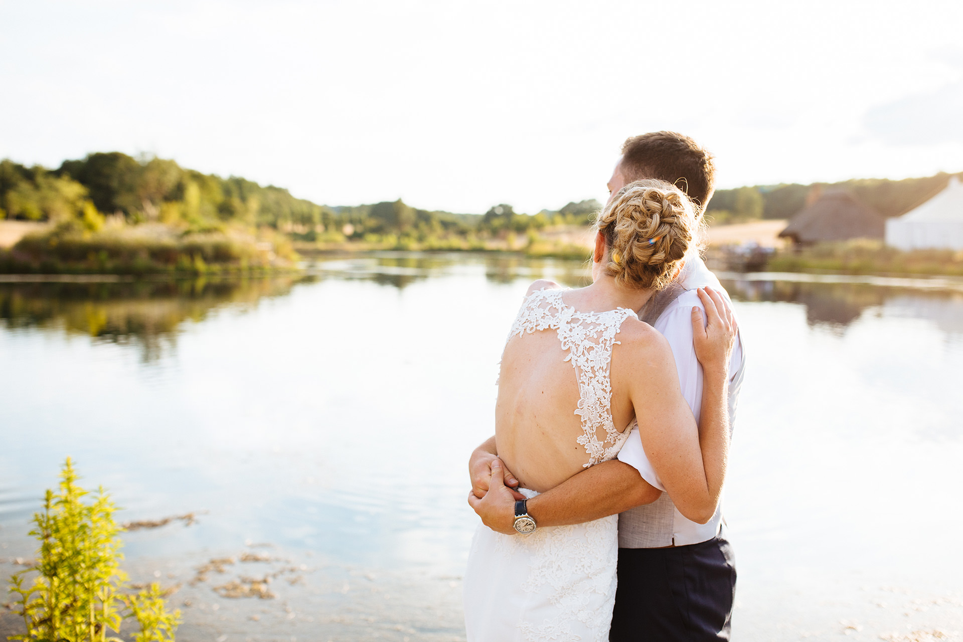 bride and groom looking out to lake at sunset at kentfield farm wedding