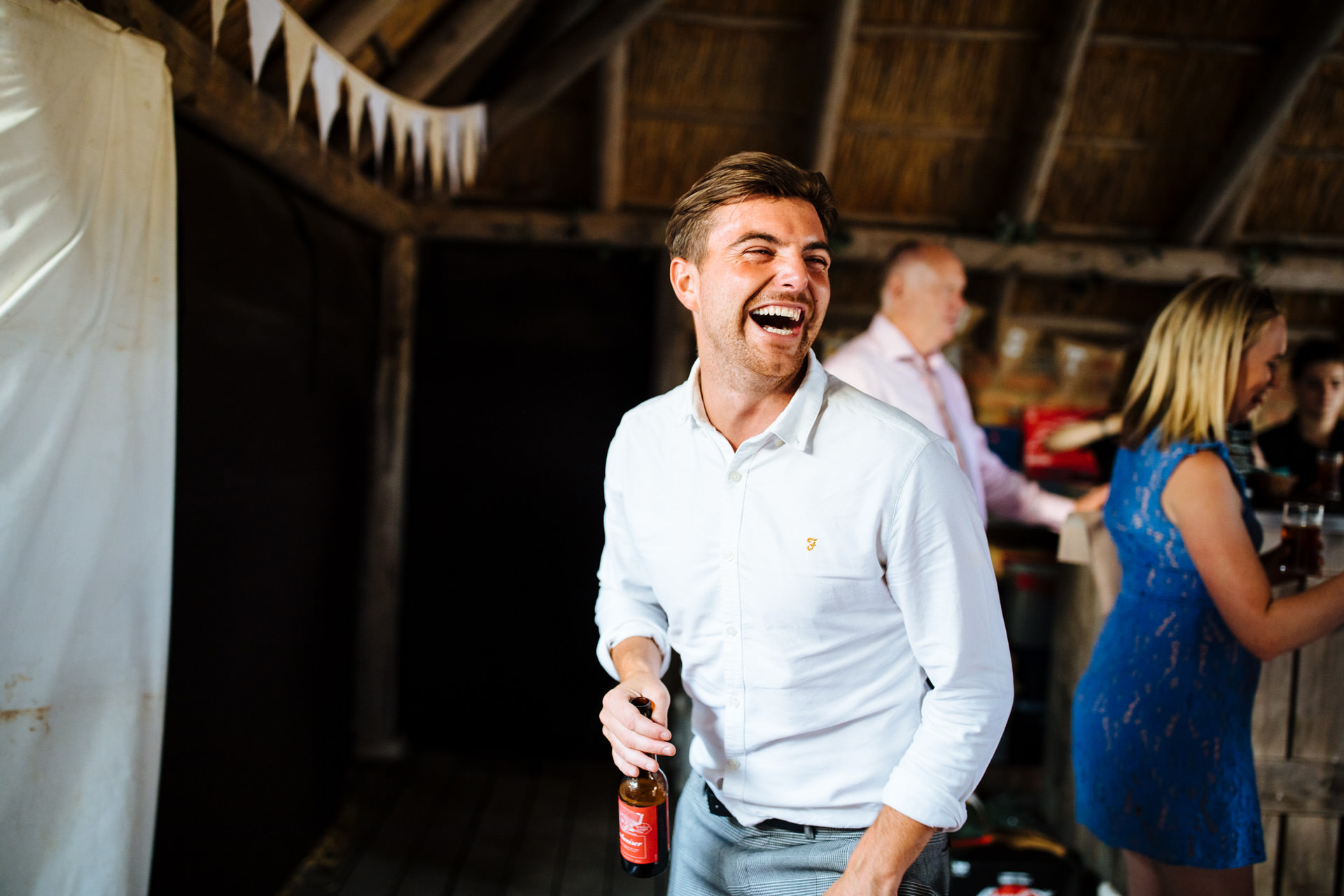 man drinking beer and laughing on the barns dancefloor
