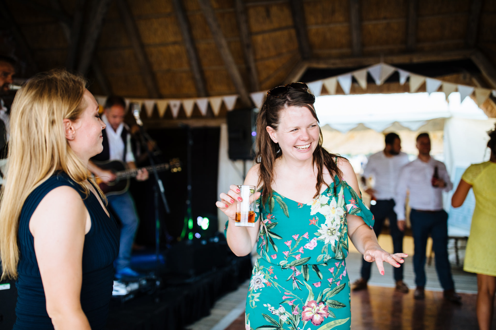 lady in green floral dress with drink in hand dancing