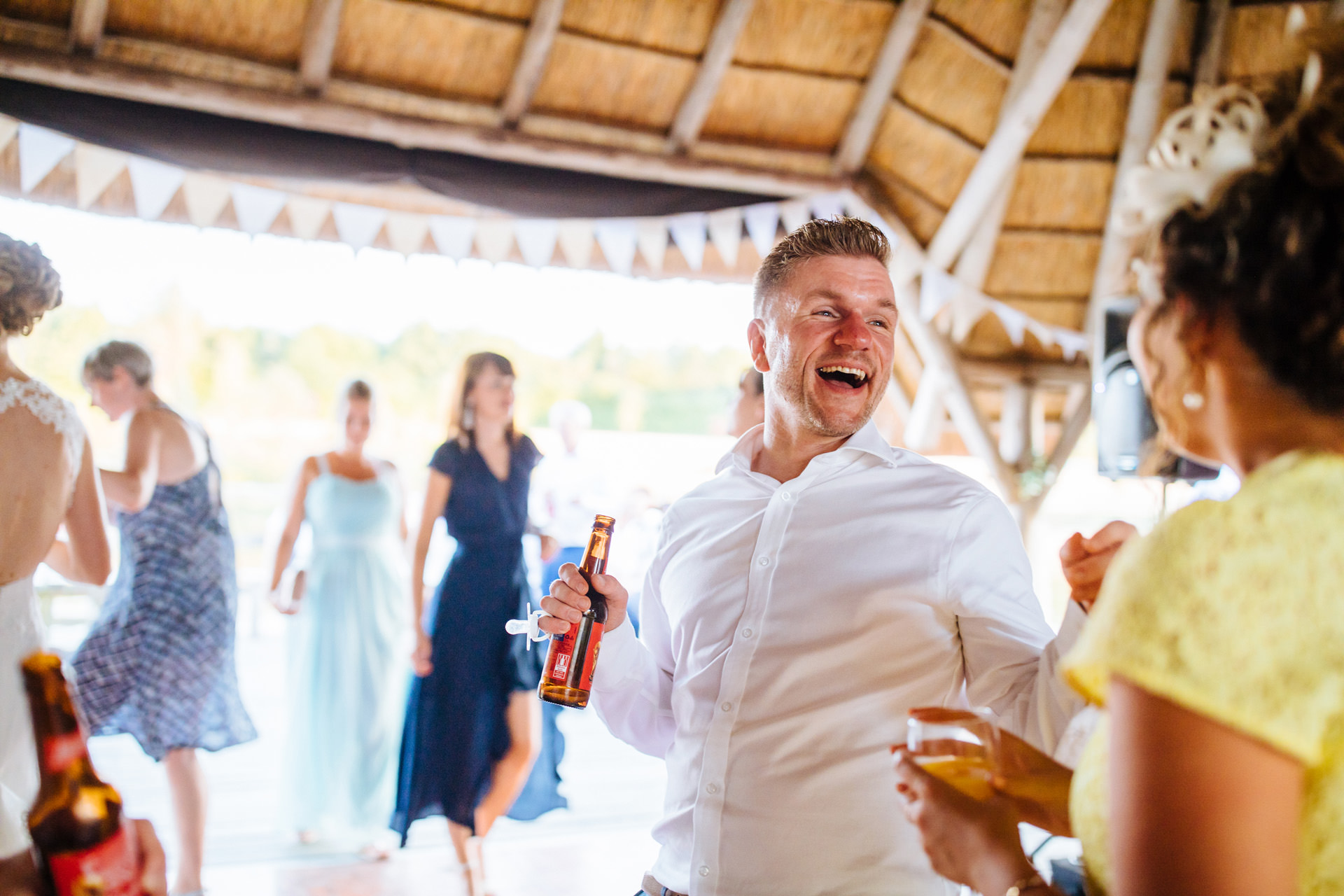 man in white shirt with Budweiser beer laughing and dancing