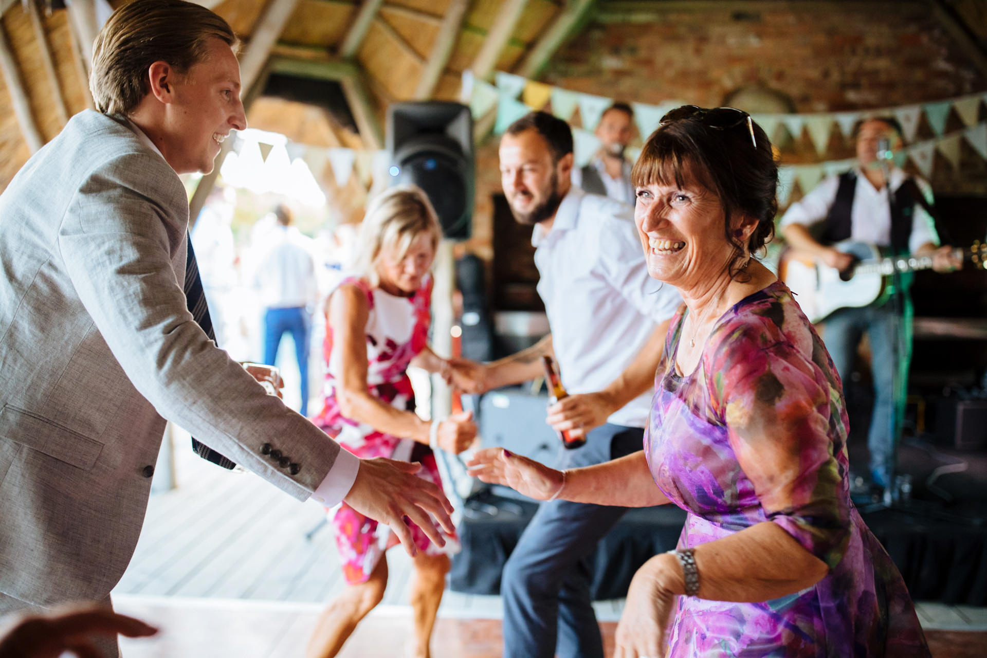 brides mum wearing purple floral dress and sunglasses dancing and laughing