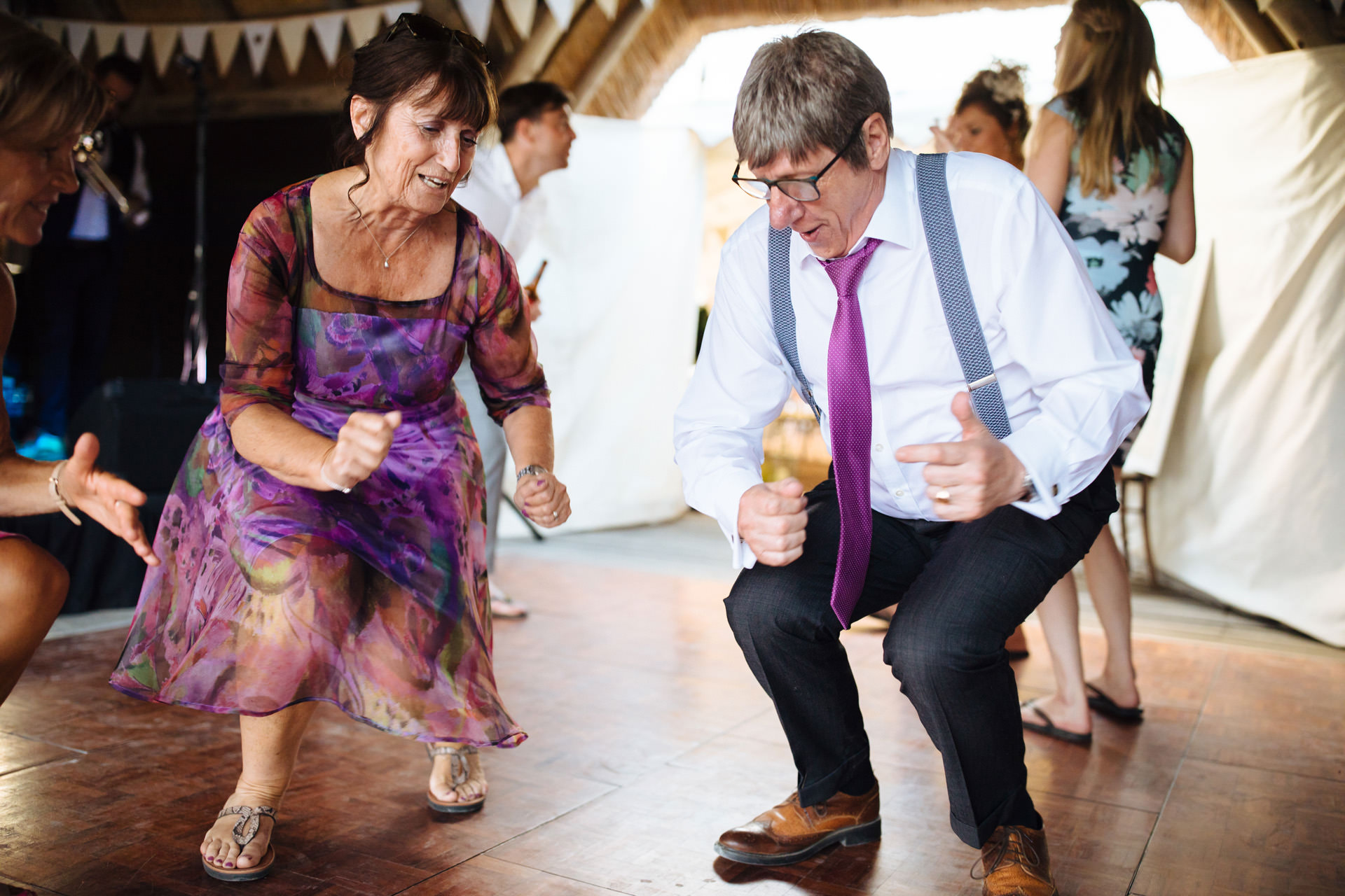 brides mum in purple floral dress and man in purple tie getting low on the dancefloor