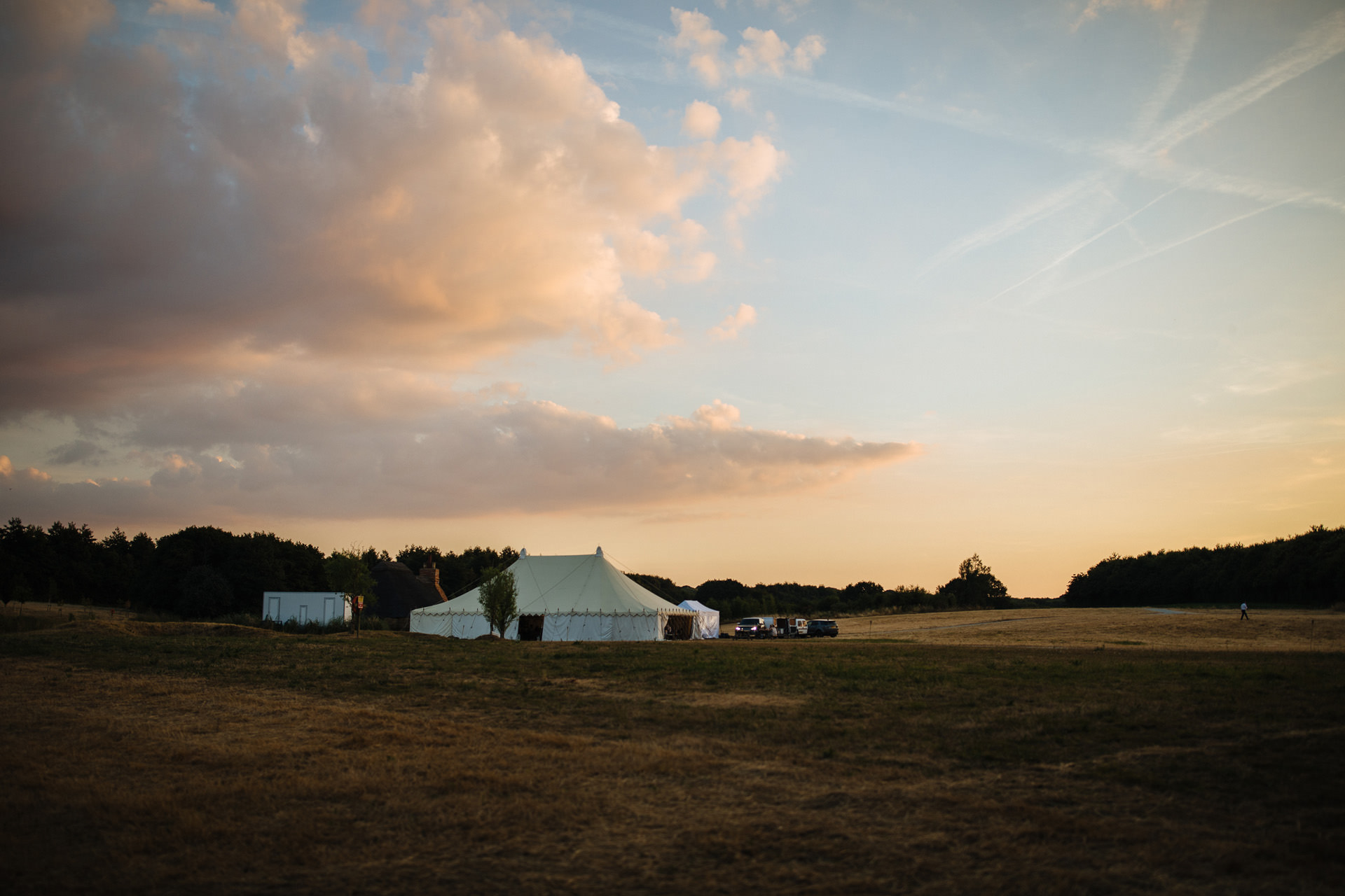 kentfield farm wedding marquee in corn field against pink sky at sunset