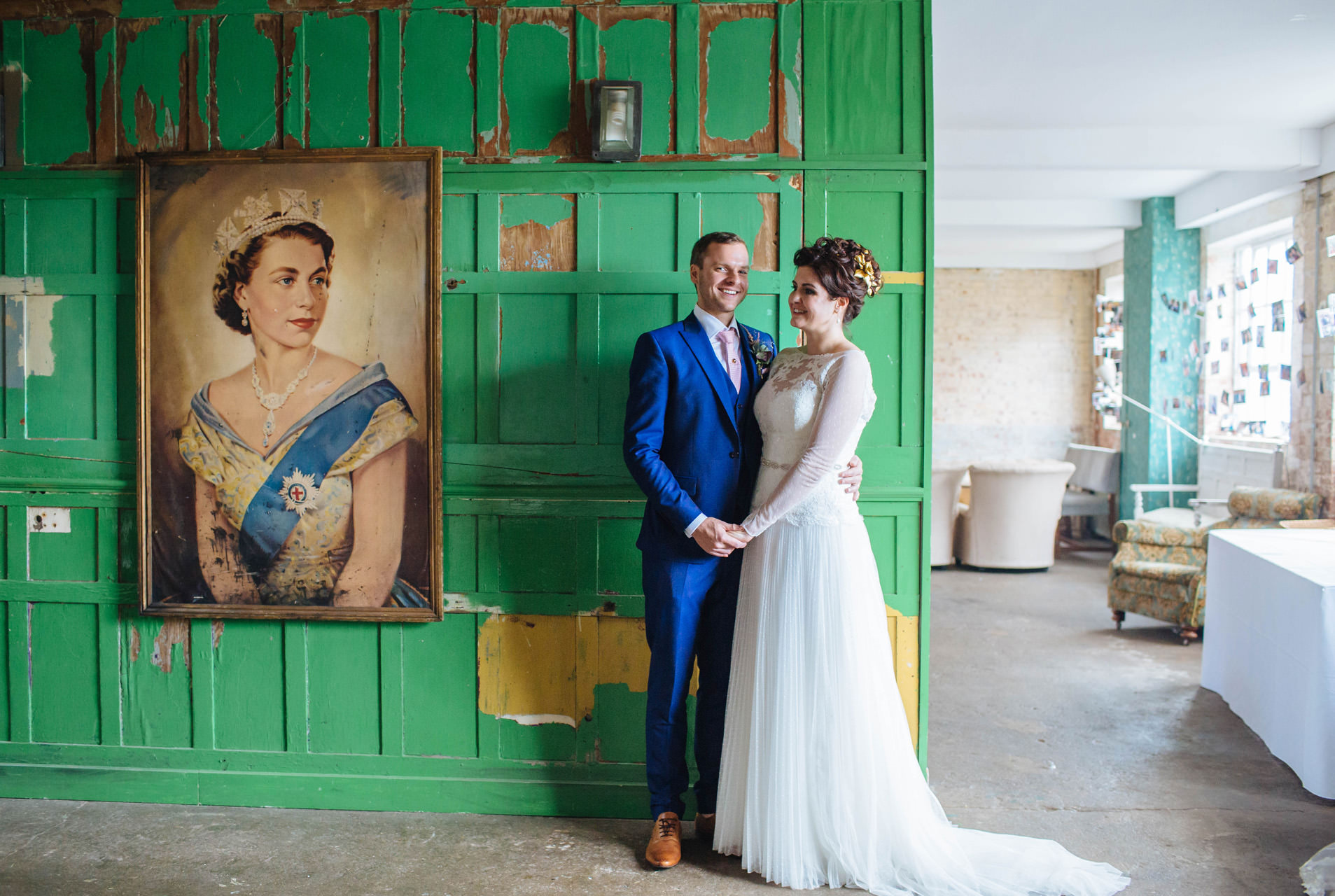 bride and groom holding hands in front of green wooden wall with a queen painting