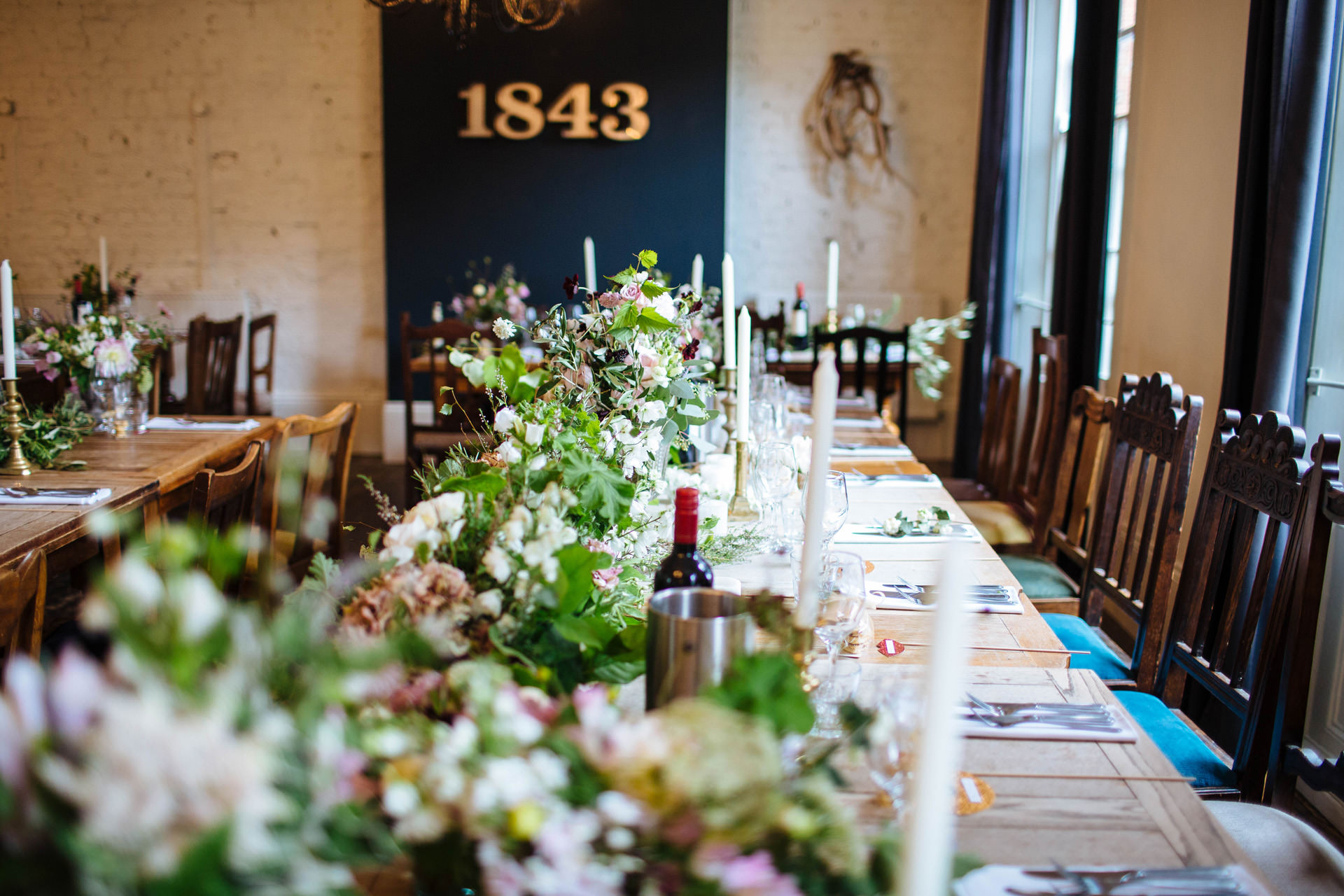 striking and wild wedding flowers with lots of greenery over rustic pub table