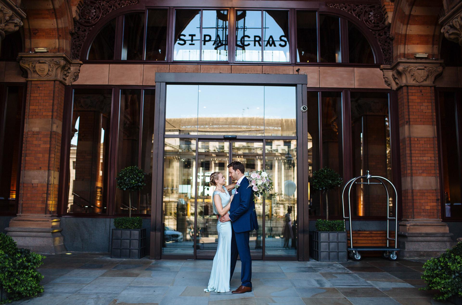 bride in light green wedding dress facing groom in front of st pancras hotel