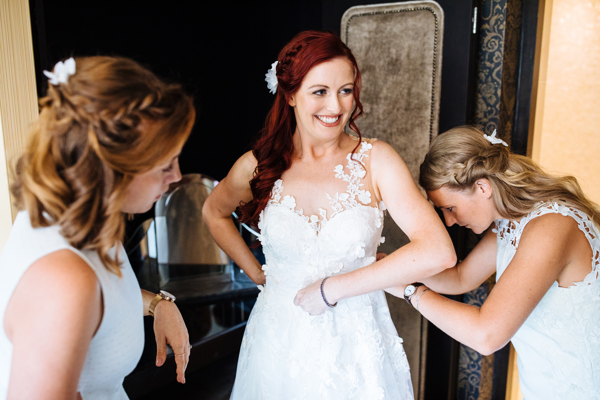bridesmaids helping bride put on her white wedding dress with floral detail