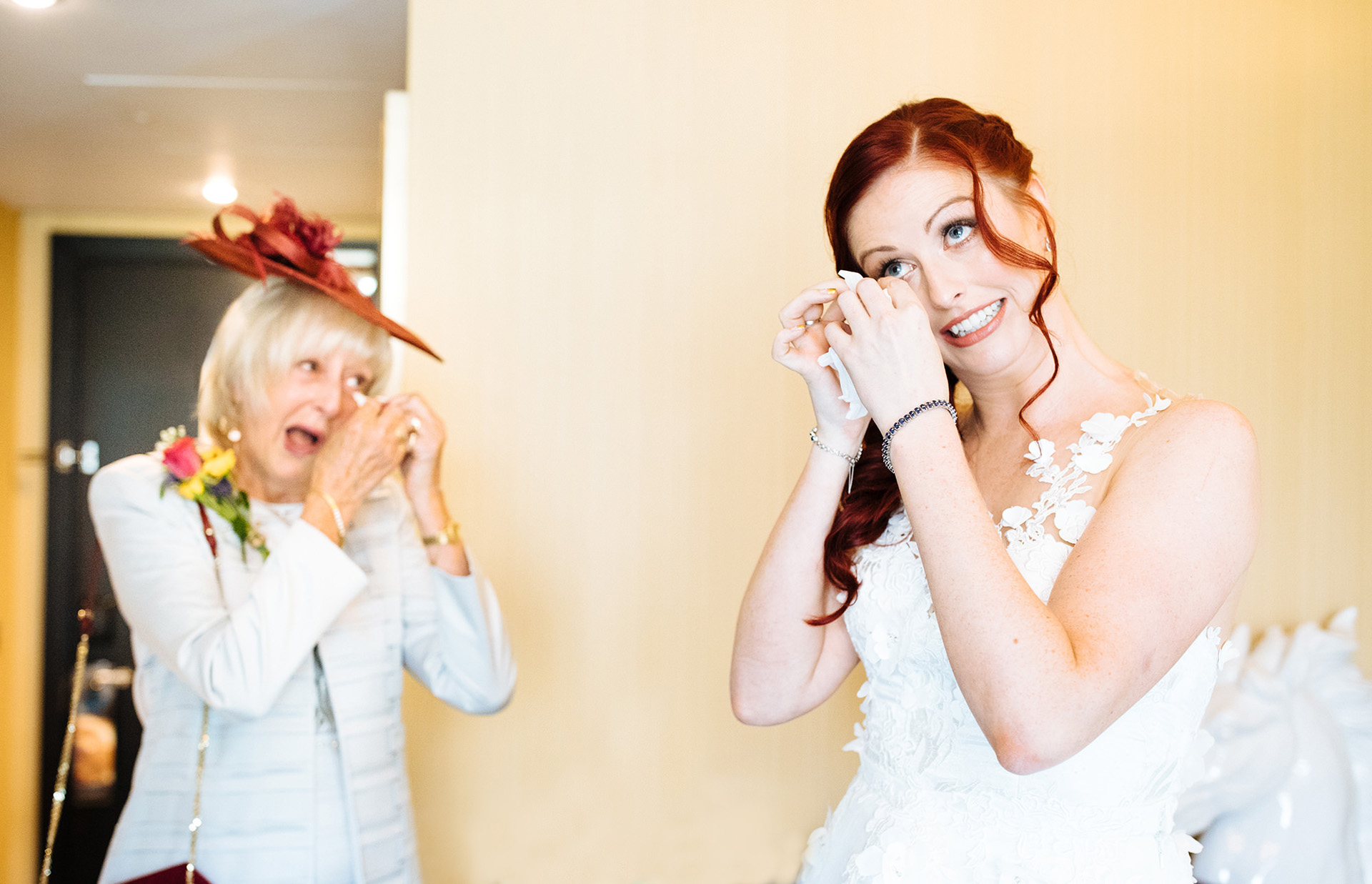 bride and her mum both wiping away happy tears after bride putting wedding dress on