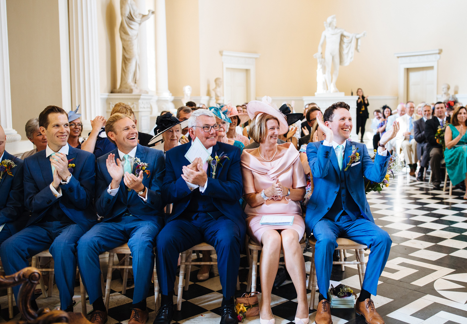 family and friends applauding the new husband and wife bride and groom saying vows in wedding ceremony in the great hall at syon park